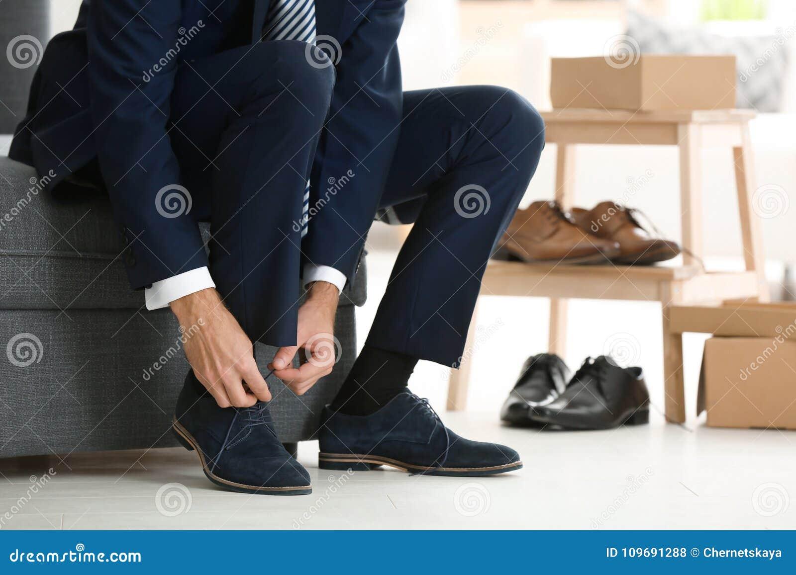 Jonge mens die op schoenen proberen