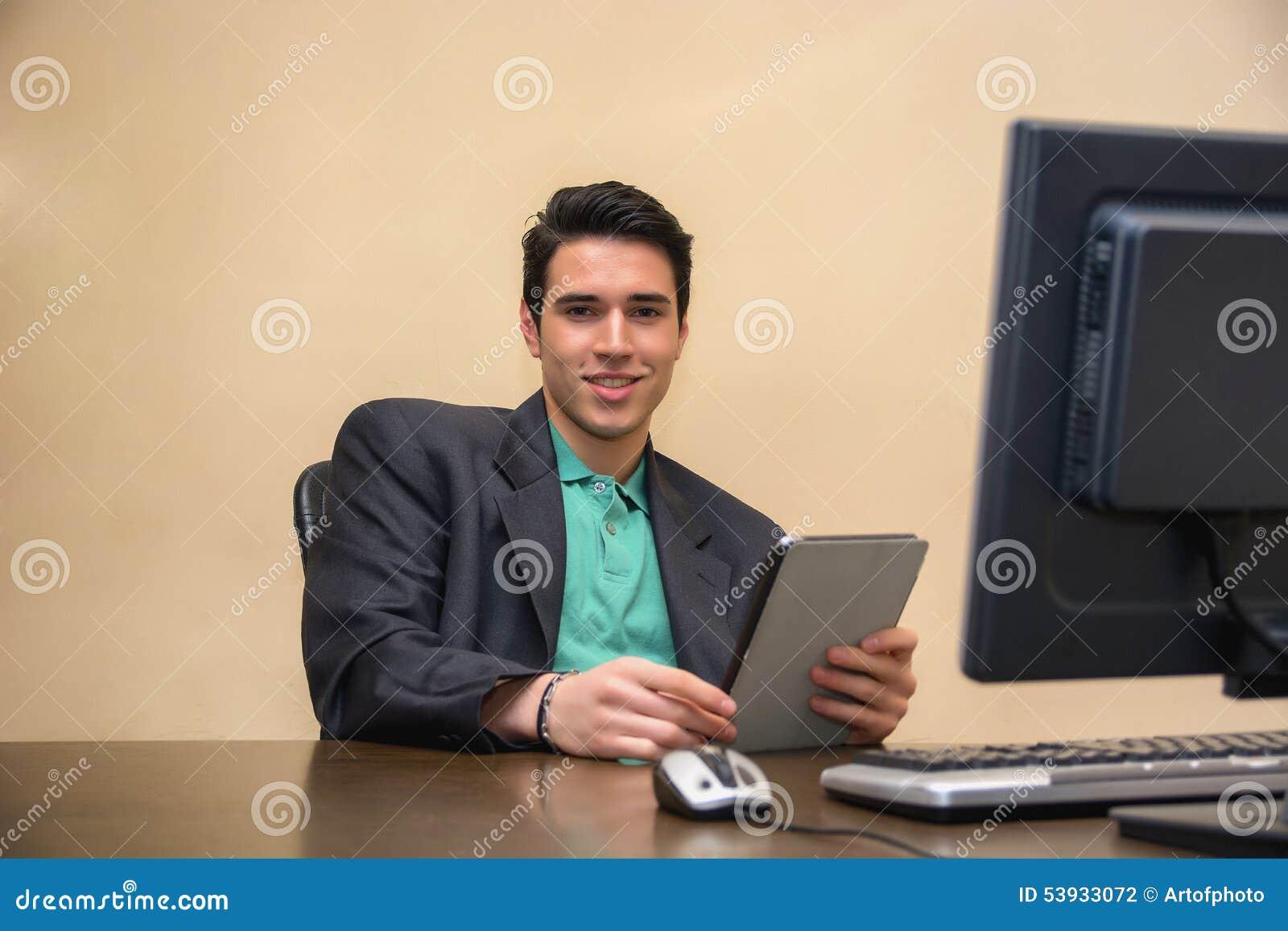 Jonge mens die pak in bureau dragen met