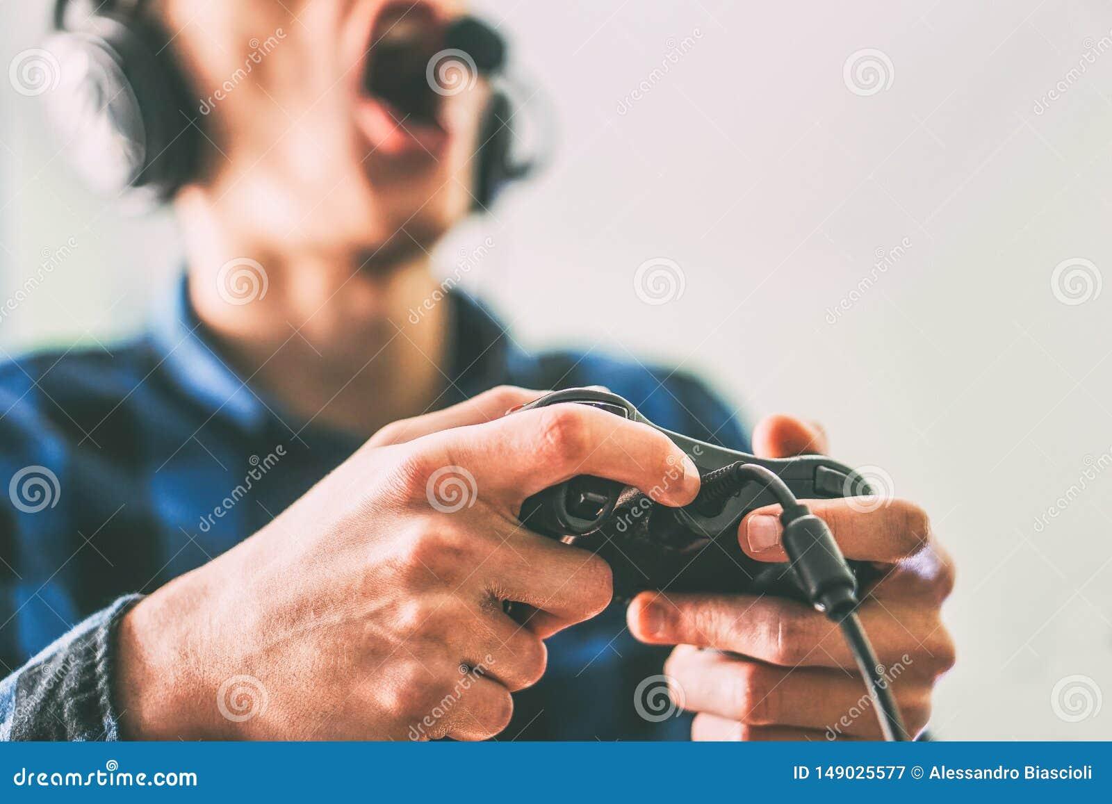 Jonge mens die pret het spelen videospelletjes online gebruikende hoofdtelefoons en microfoon hebben - sluit omhoog mannelijke ha