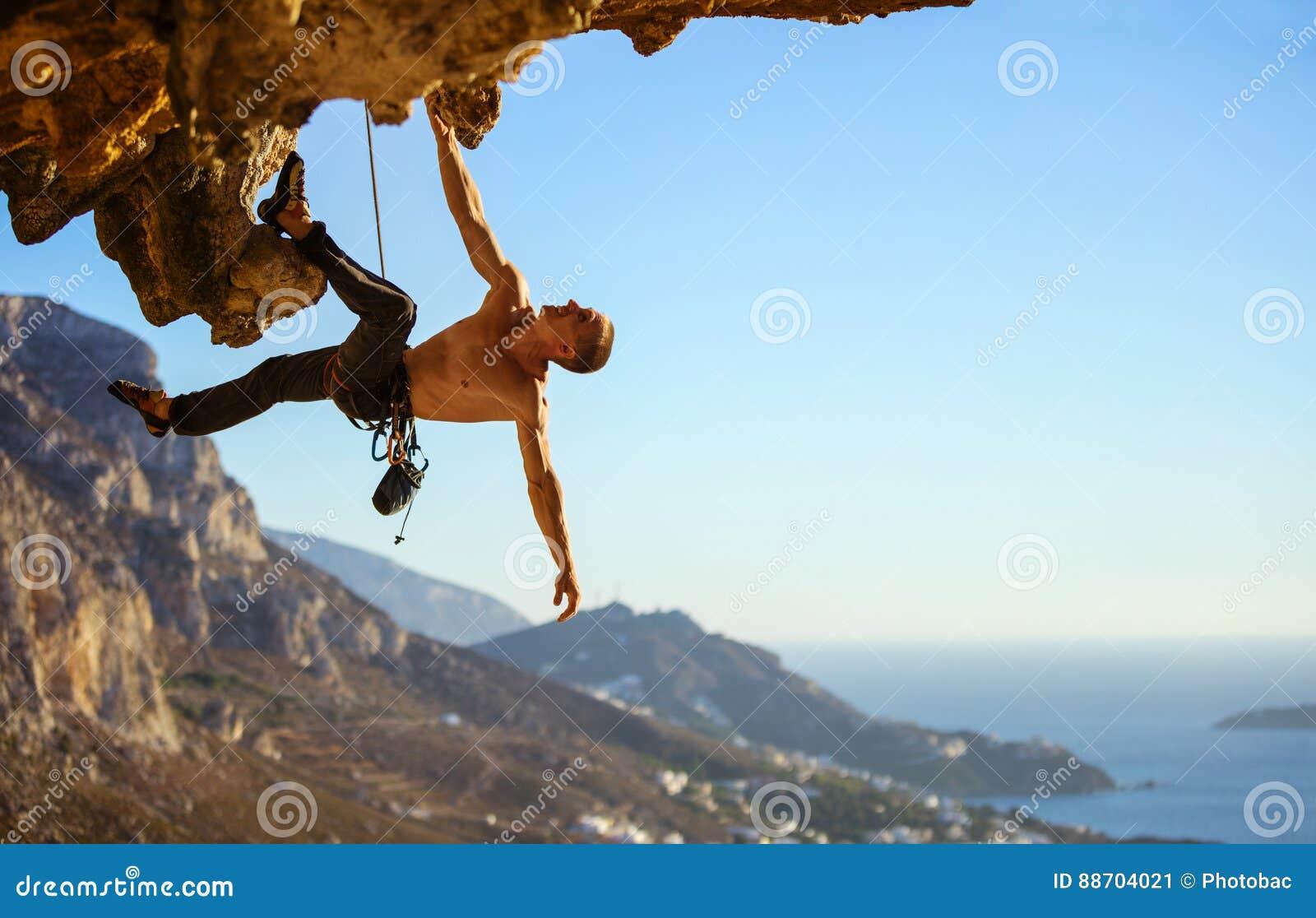 Jonge mens die richel op klip worstelen te beklimmen