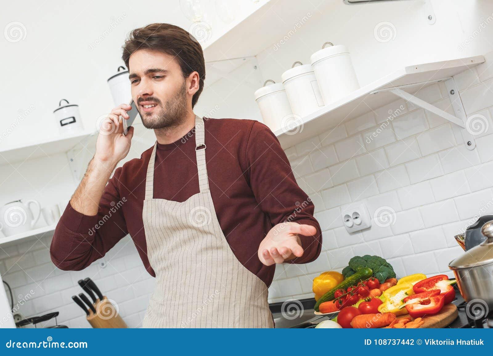 Jonge mens die romantisch diner thuis telefoongesprek koken
