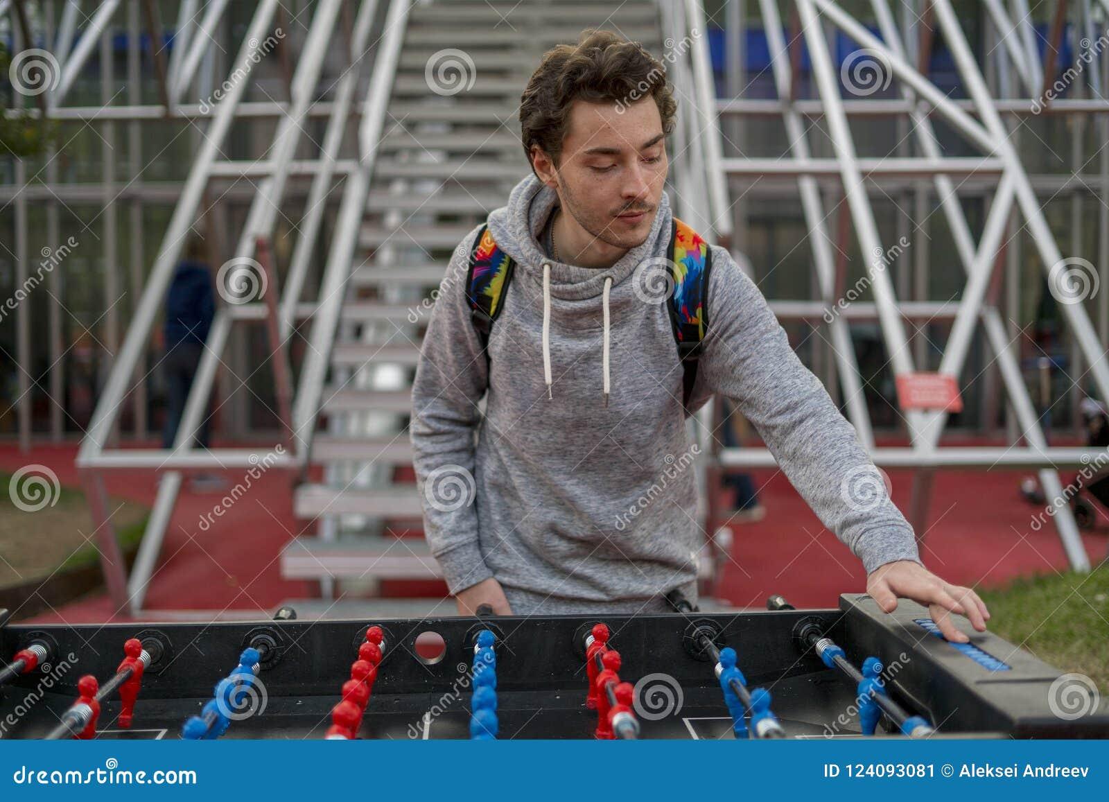 Jonge mens die tablefootball en een score in park in Moskou veranderen spelen