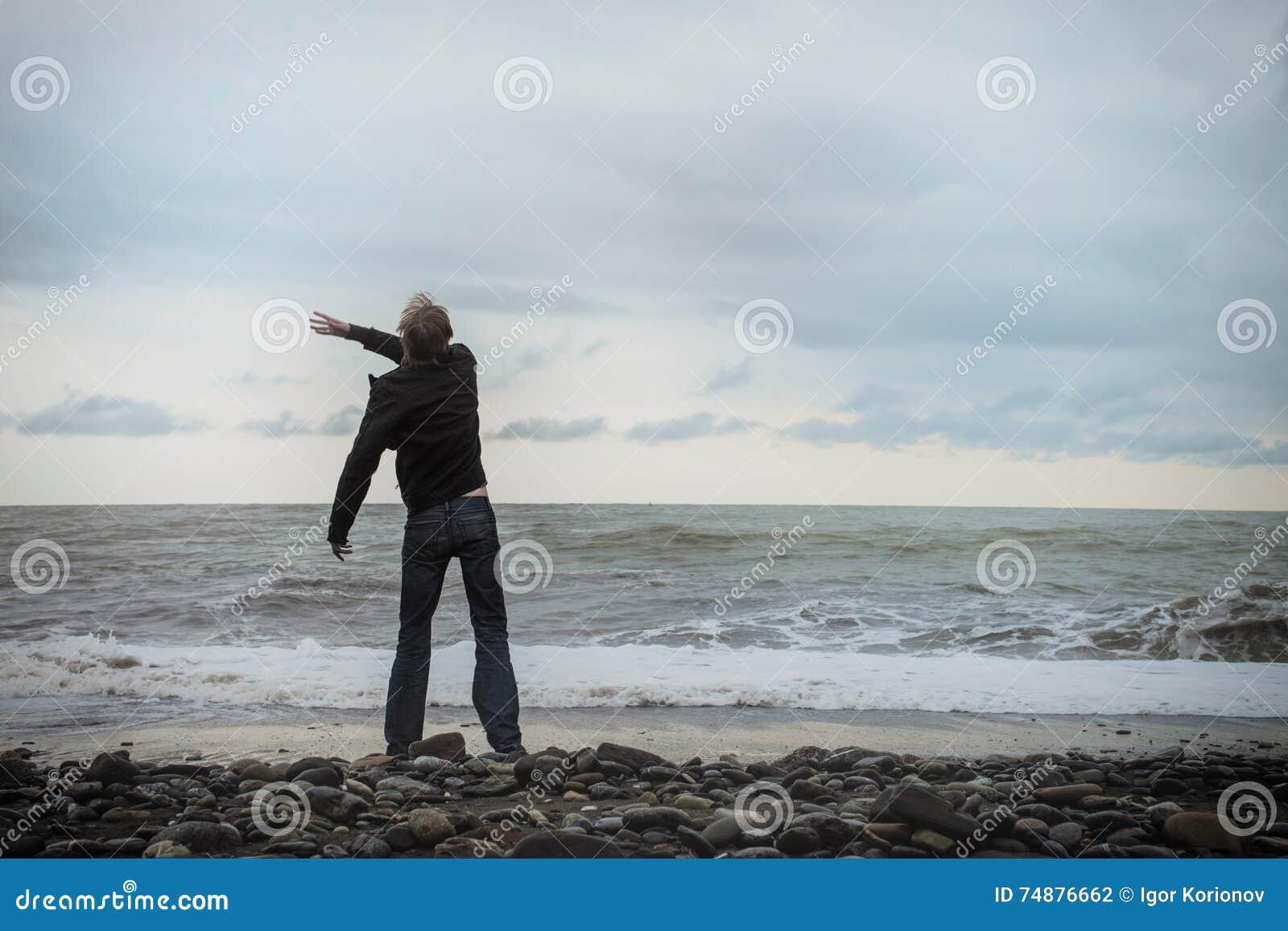 Jonge mens die zich op de overzeese kust bevinden