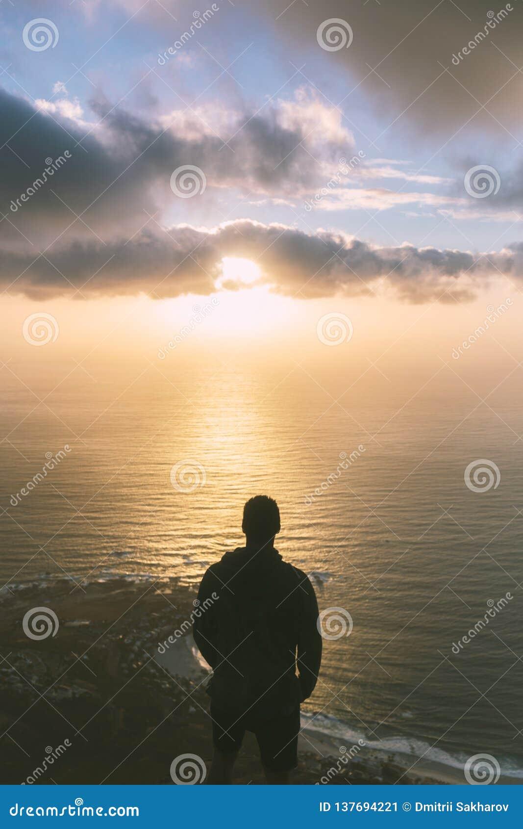 Jonge mens die zich op de rand bij de bovenkant van de hoofdberg van de Leeuw in Cape Town bevinden