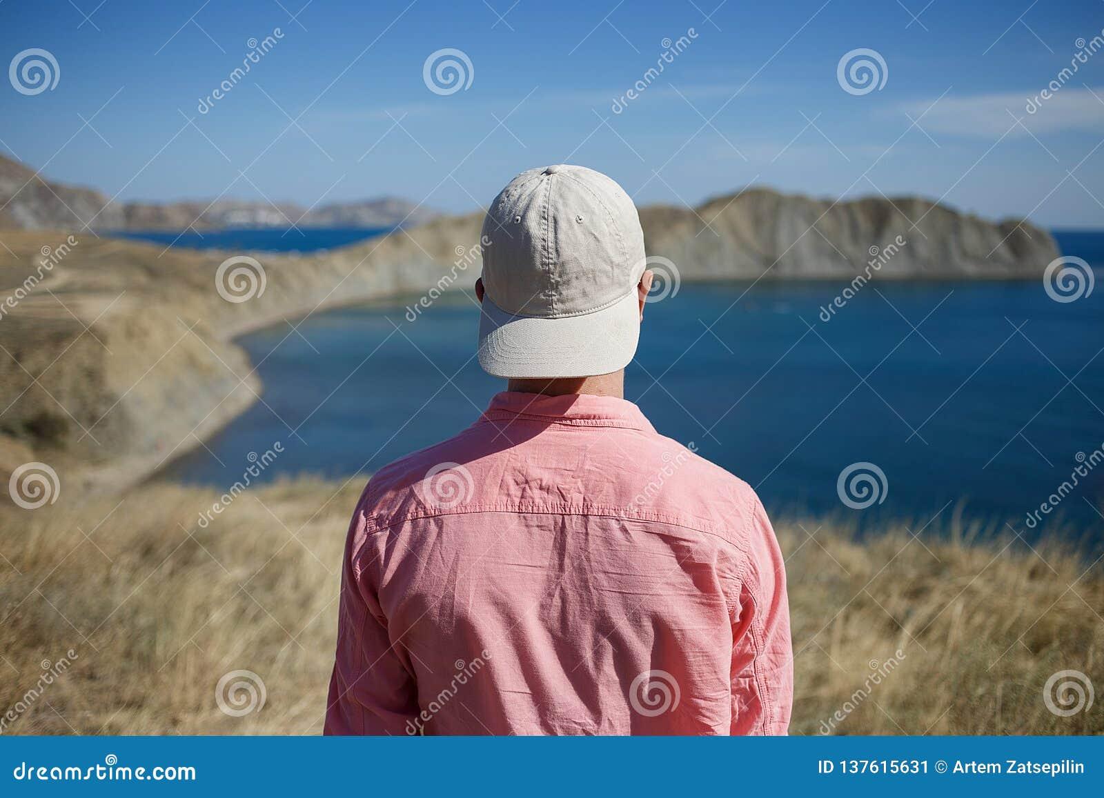 Jonge mens die zich op een bergkust bevinden die aan het overzees kijken