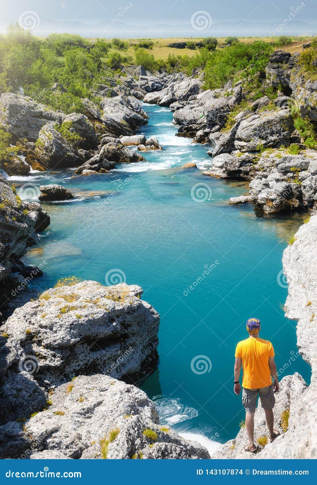 Jonge mens die zich op een rots aove een blauwe stroom bevinden die aan een groen gebied toevloeien