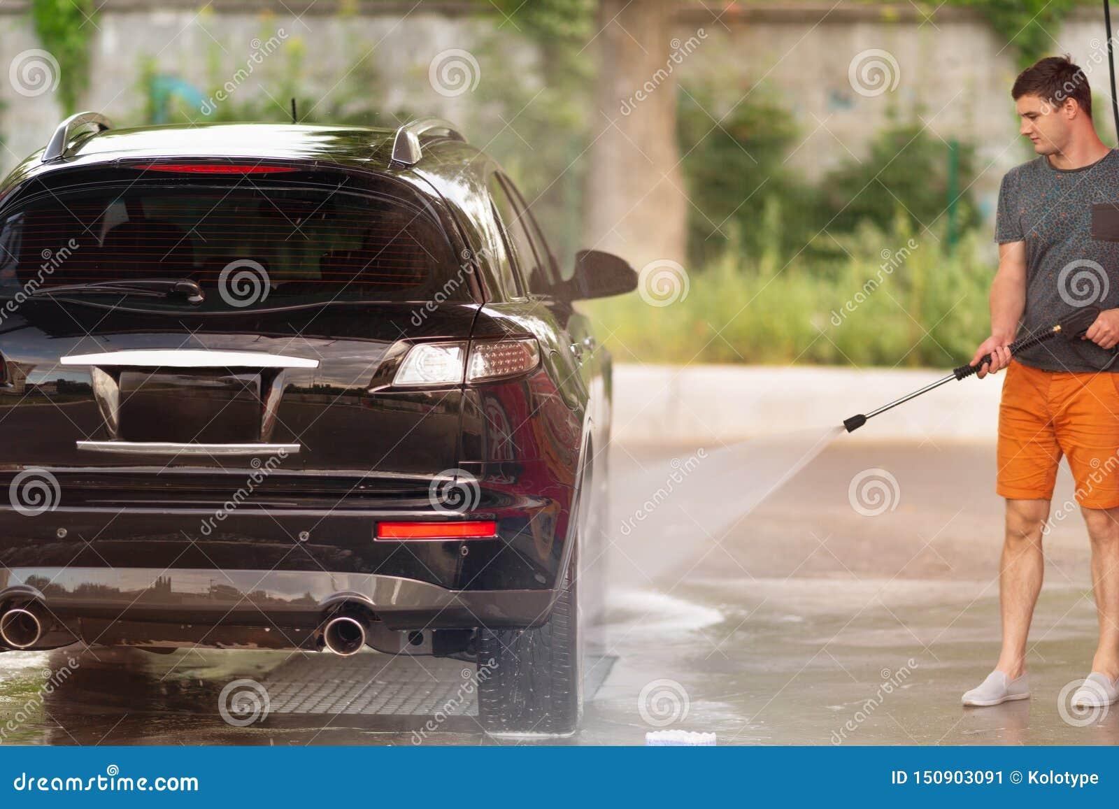 Jonge mens die zijn auto wassen bij de autowasserette