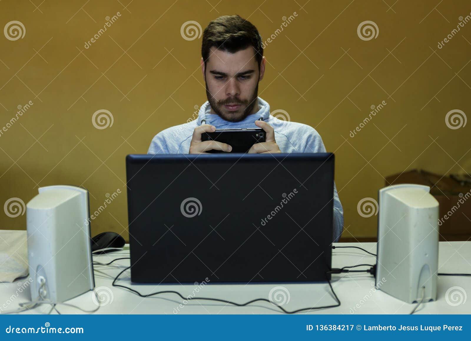 Jonge mens die zijn mobiel, tablet, laptop en hoofdtelefoons met behulp van