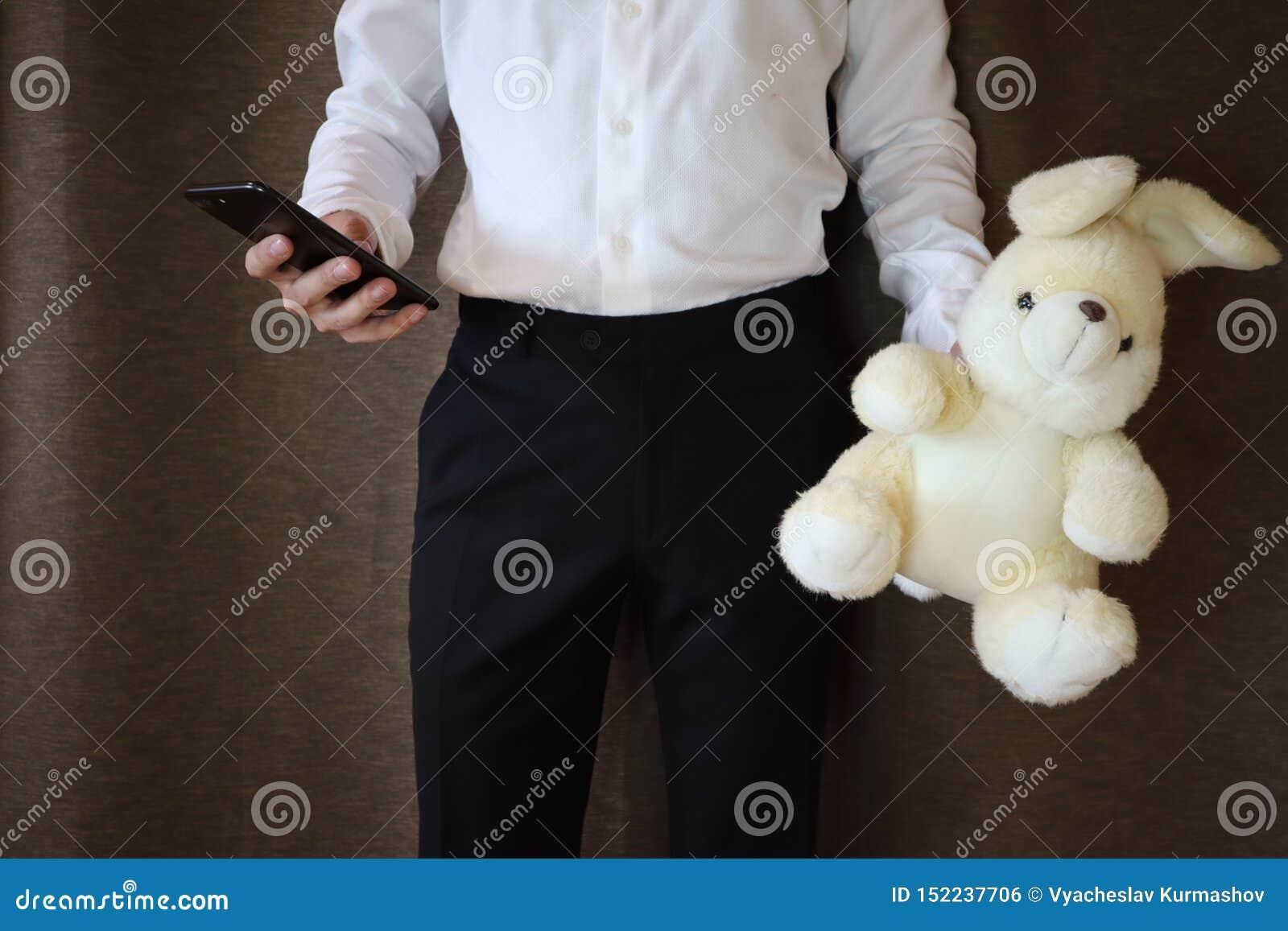 Jonge mens in een wit overhemd en een zwarte broek die stuk speelgoed hazen en een telefoon houden Een mens met een groot stuk sp