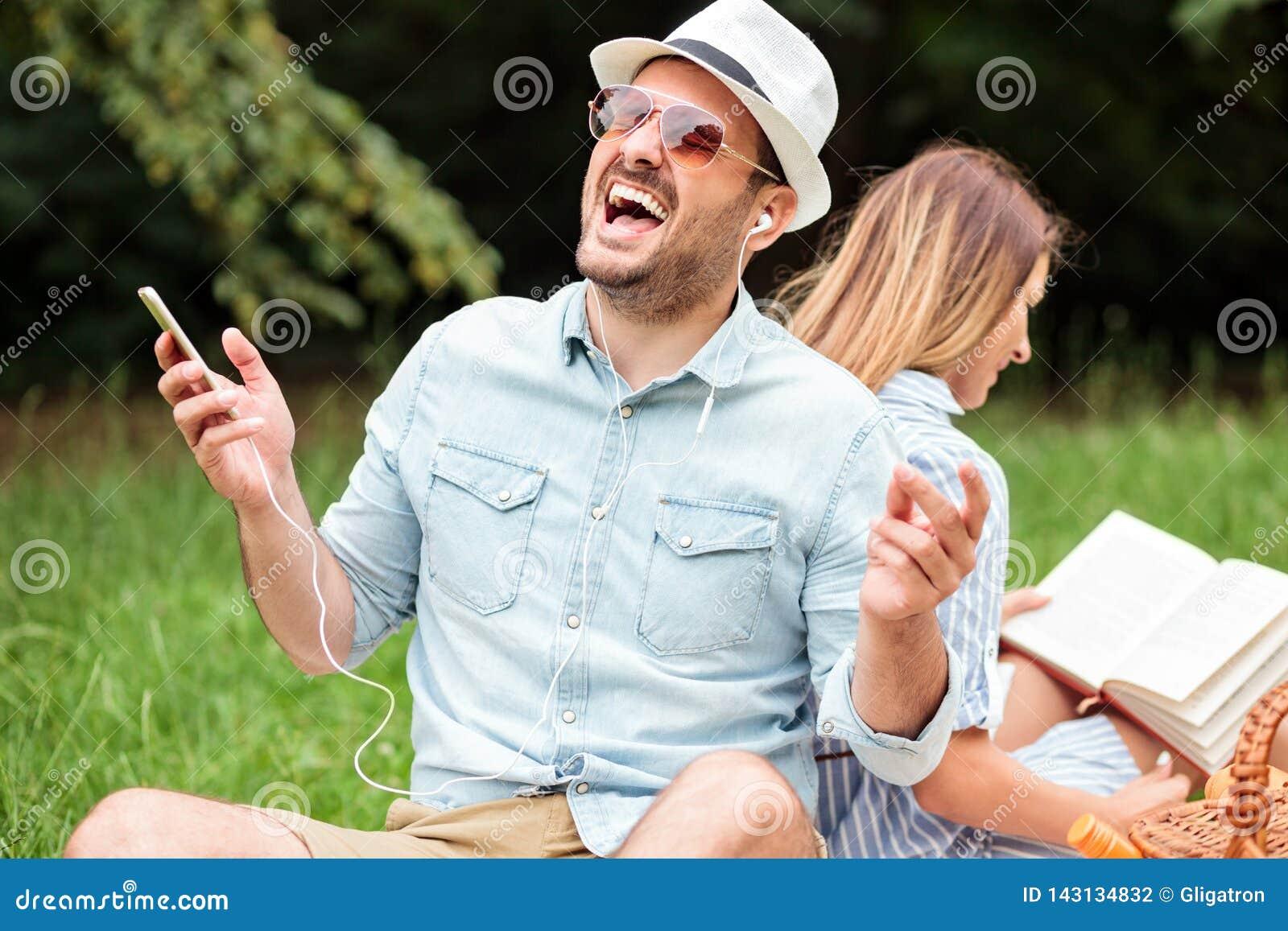 Jonge mens genieten die aan zijn favoriet lied luisteren Zitten rijtjes met zijn meisje dat een boek leest