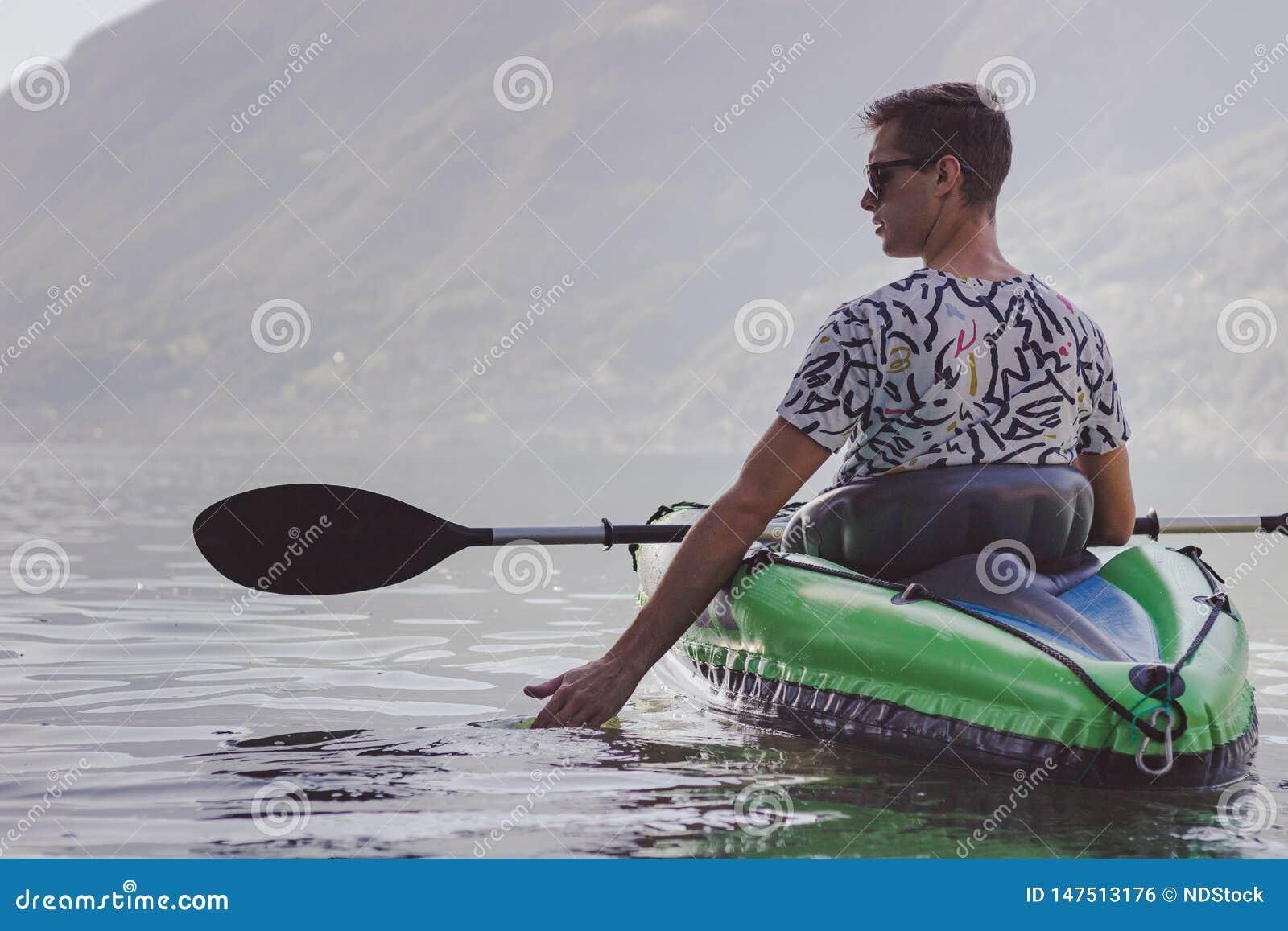 Jonge mens het kayaking op het meer