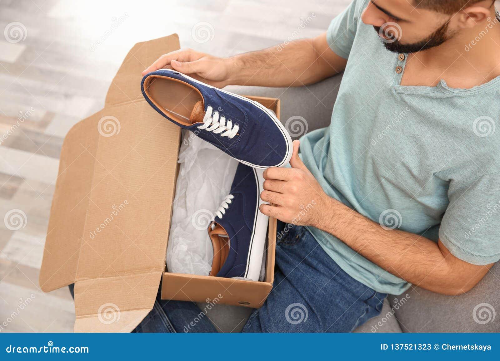 Jonge mens het openen pakket met schoenen thuis