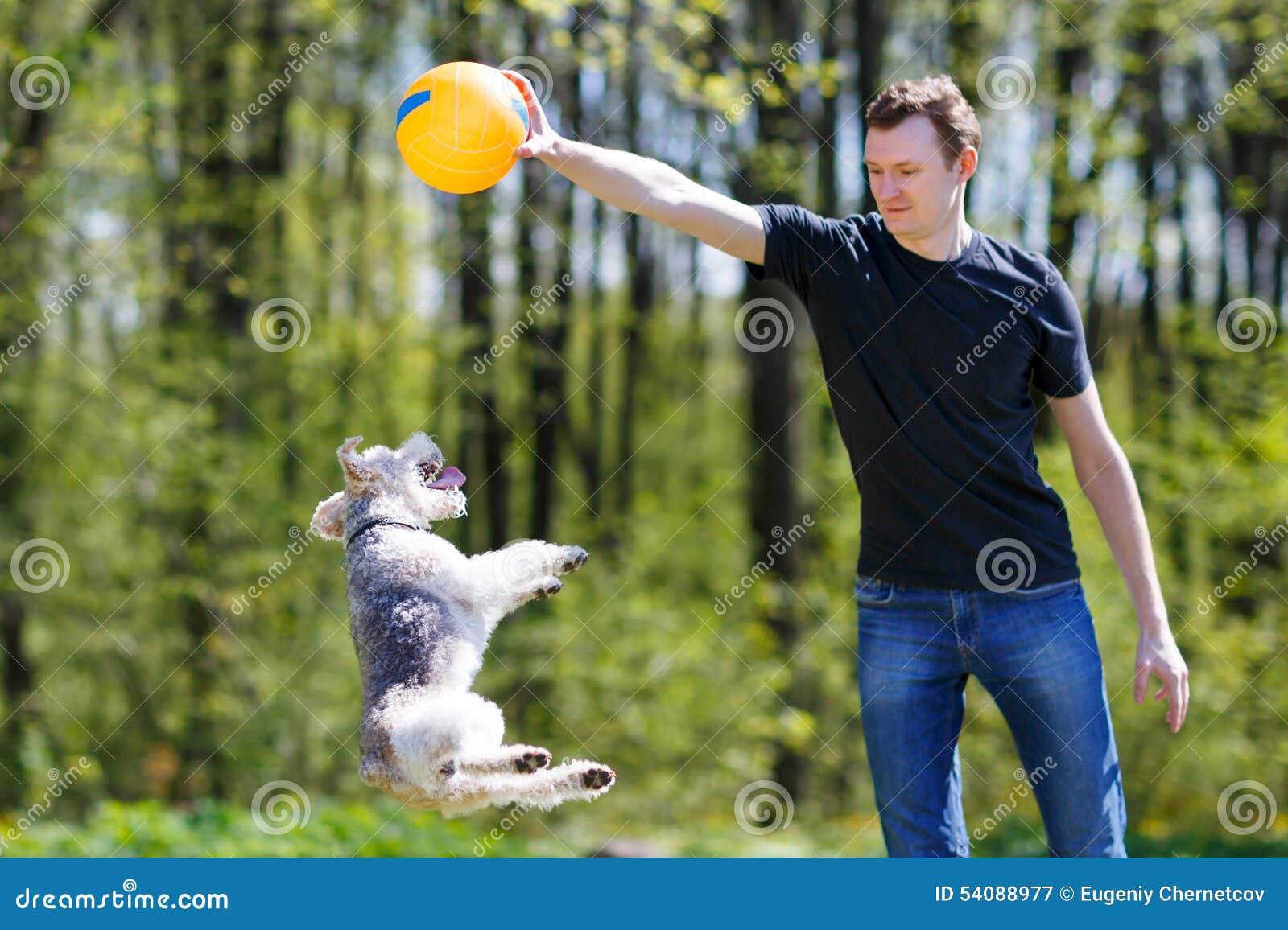 Jonge mens het spelen met zijn hond