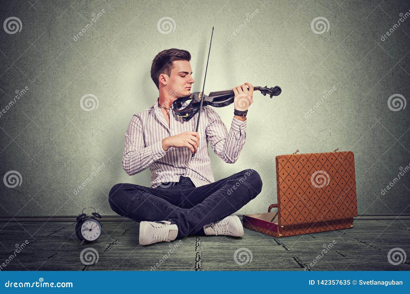 Jonge mens het spelen op een zwarte elektronische viool