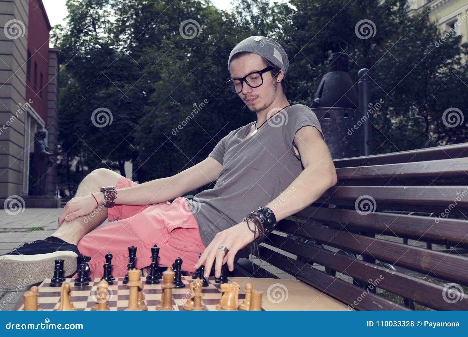 Jonge mens het spelen schaak in het park Het zitten op een bank maakt hij een beweging