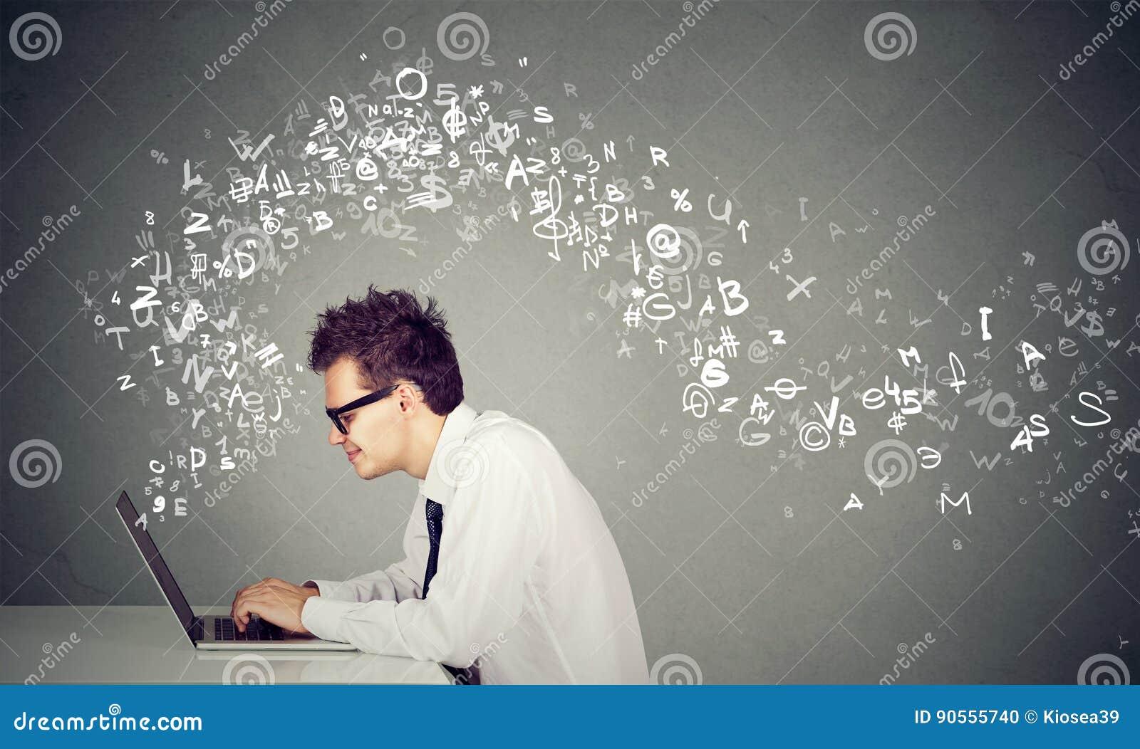 Jonge mens het typen op laptop de brieven die van het computeralfabet wegvliegen