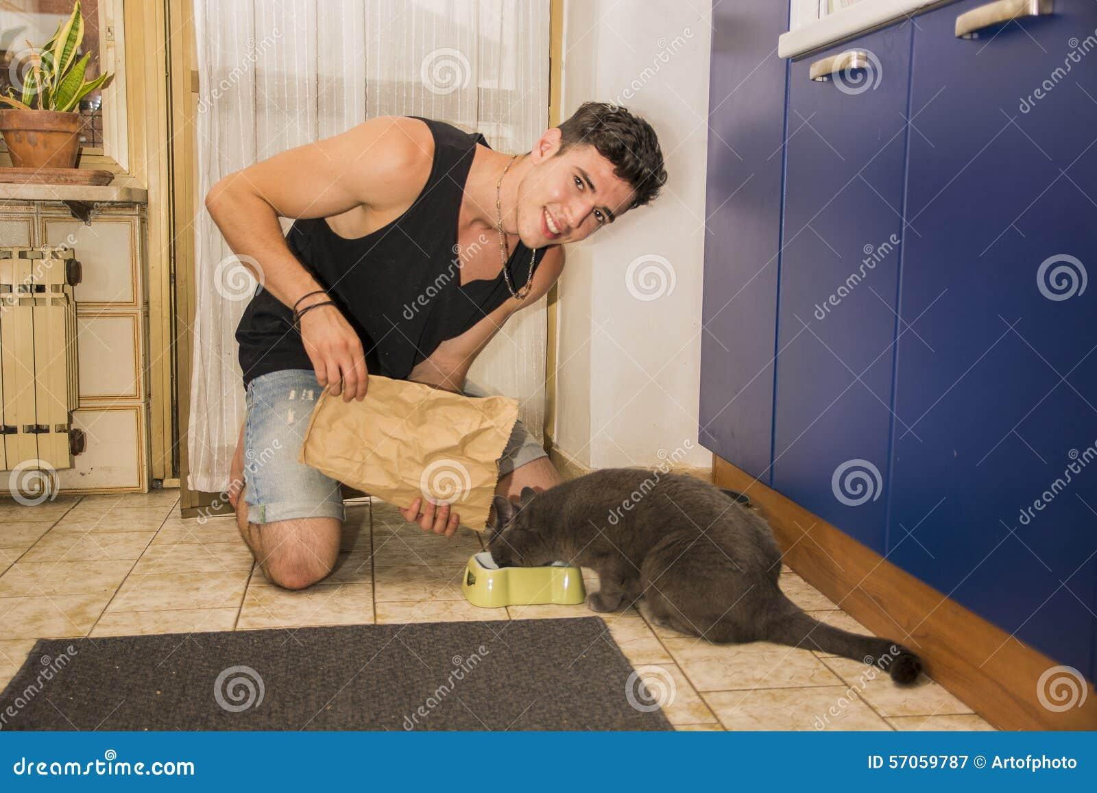Jonge Mens het Vullen Huisdierenkom met Droog Voedsel voor Kat