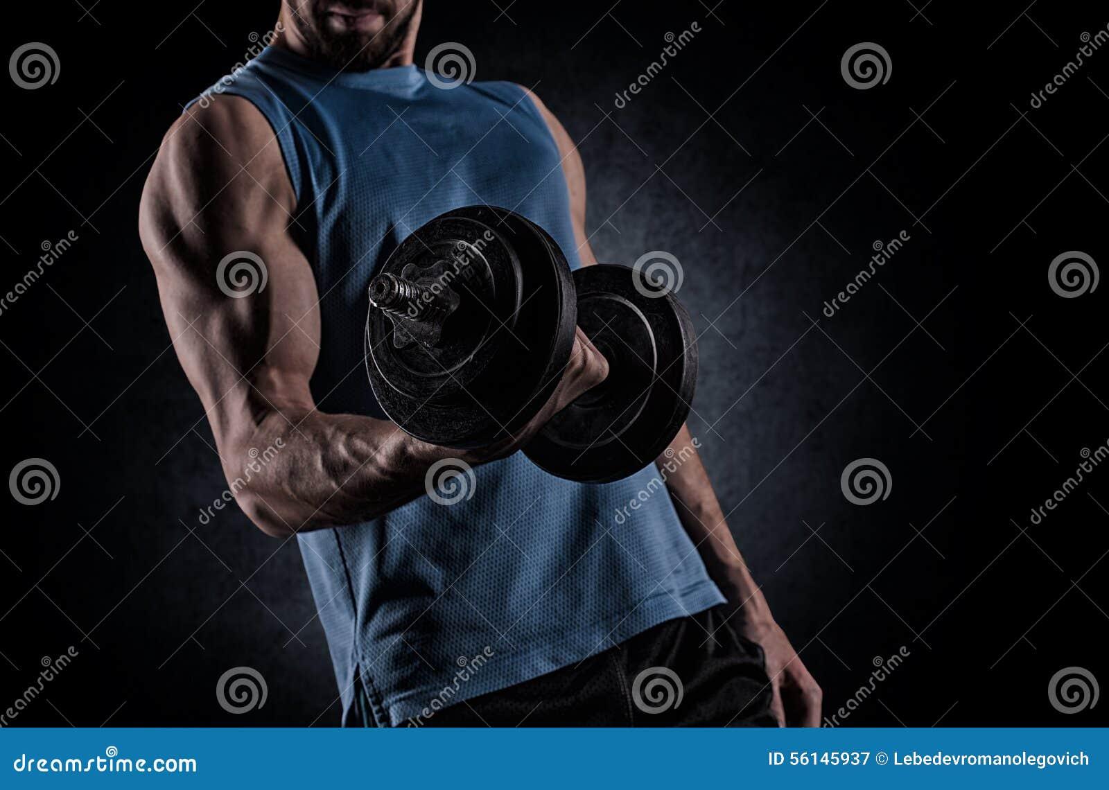 Jonge mens met de spieren van de domoorverbuiging over grijze achtergrond