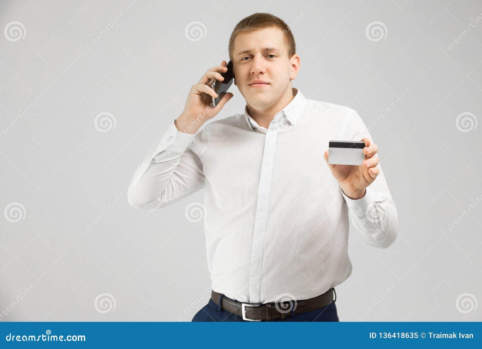 Jonge mens met een Betaalpas en mobiele die telefoontribunes op lichte achtergrond wordt geïsoleerd