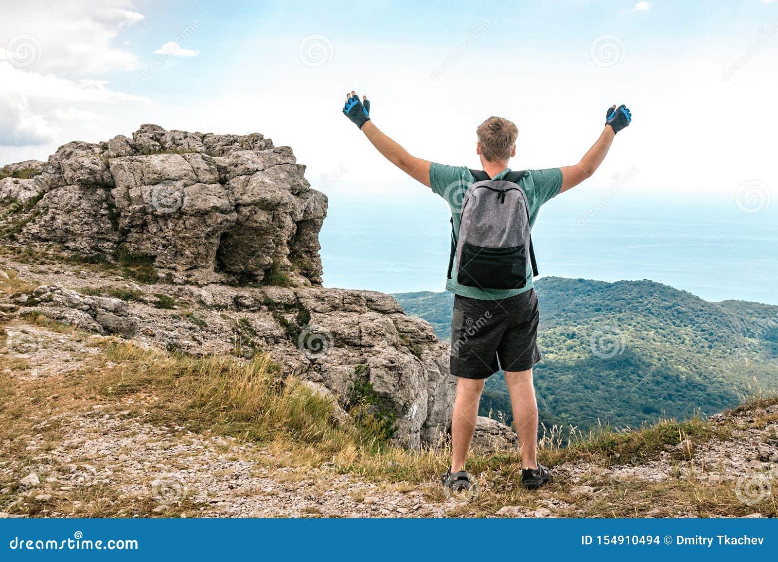 Jonge mens met een rugzak bovenop klip die van mening van aard genieten Bergen en Overzees