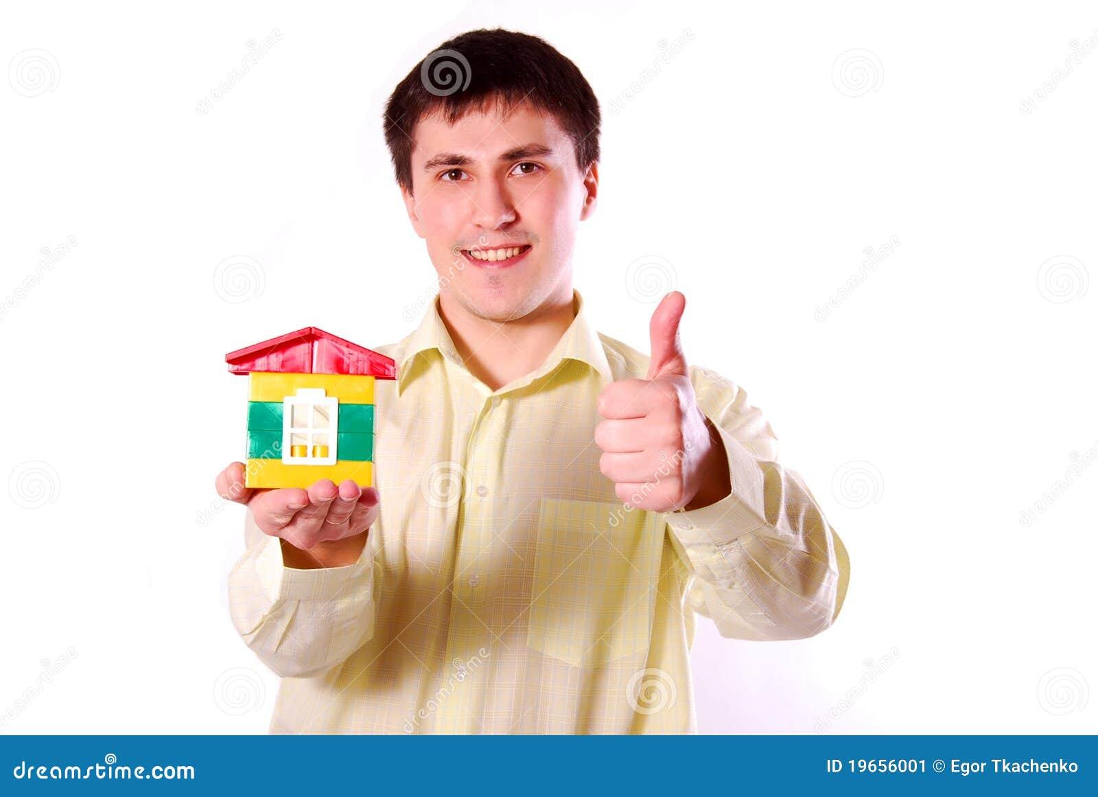 Jonge mens met het model van het huis.
