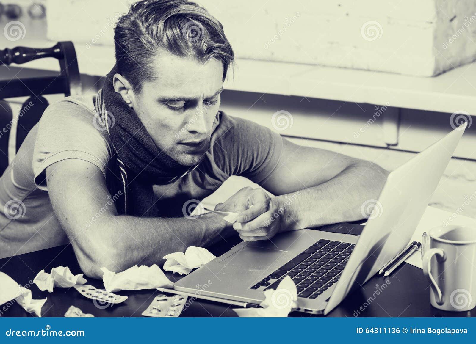 Jonge mens met thermometerzieken die zijn neus in zijn zwart wit ...