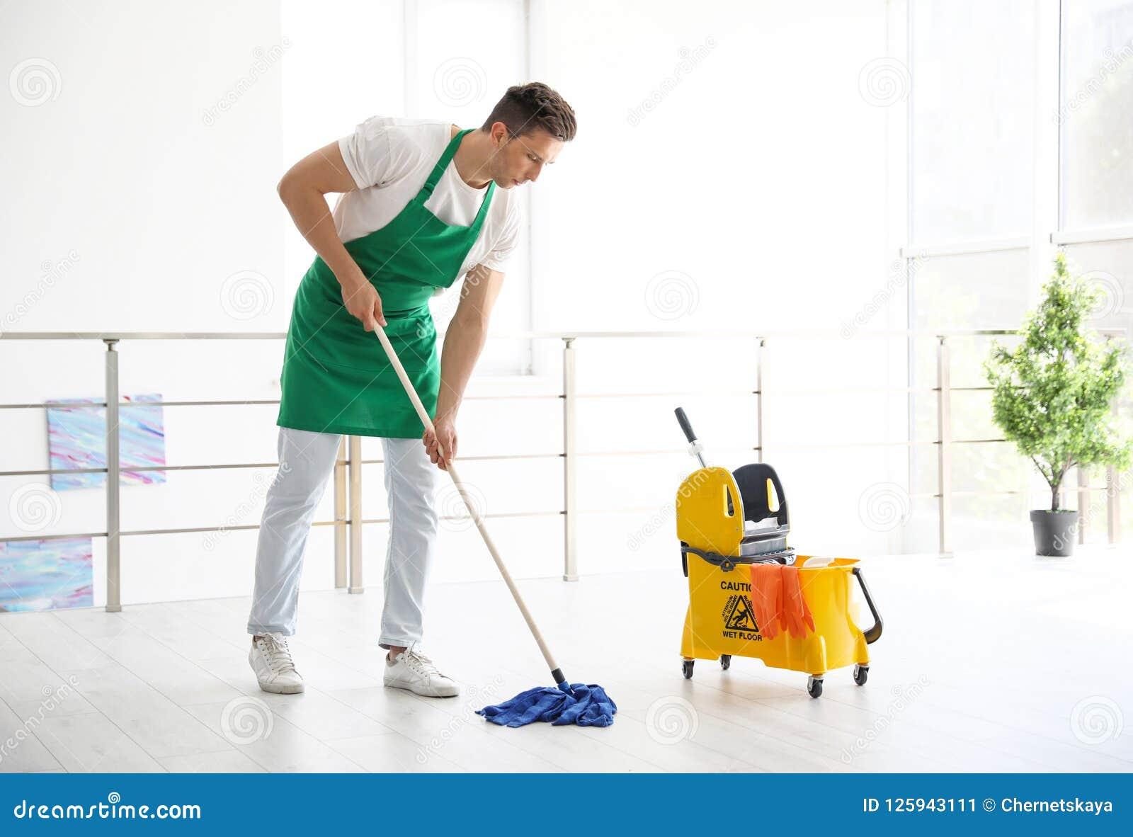 Jonge mens met zwabber schoonmakende vloer