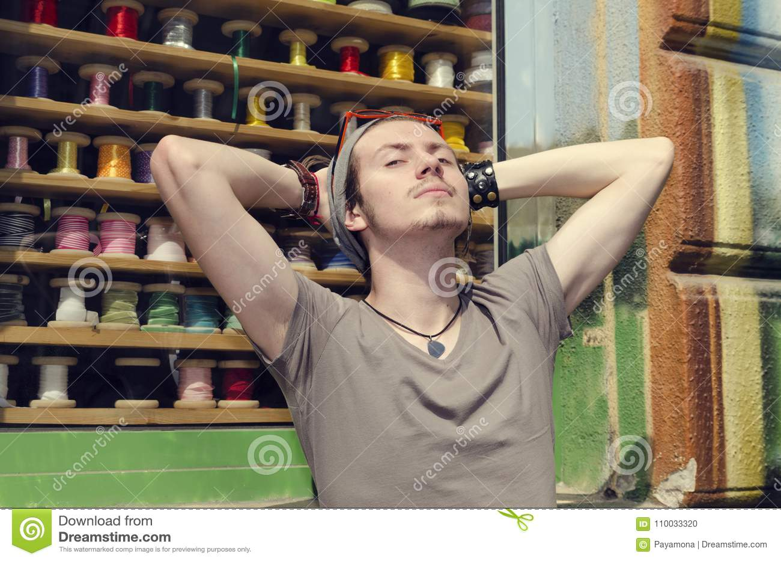Jonge mens op een straat die van de Zon voor kleurrijke lintwinkel genieten