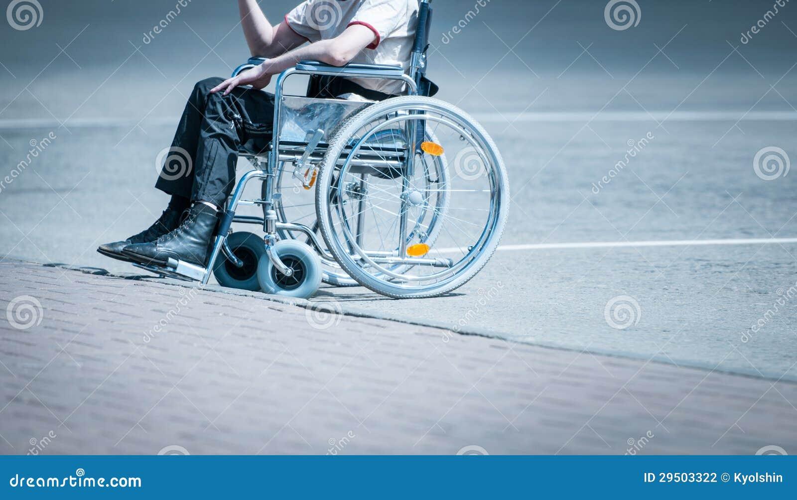 Jonge mens in rolstoel op de alleen weg.