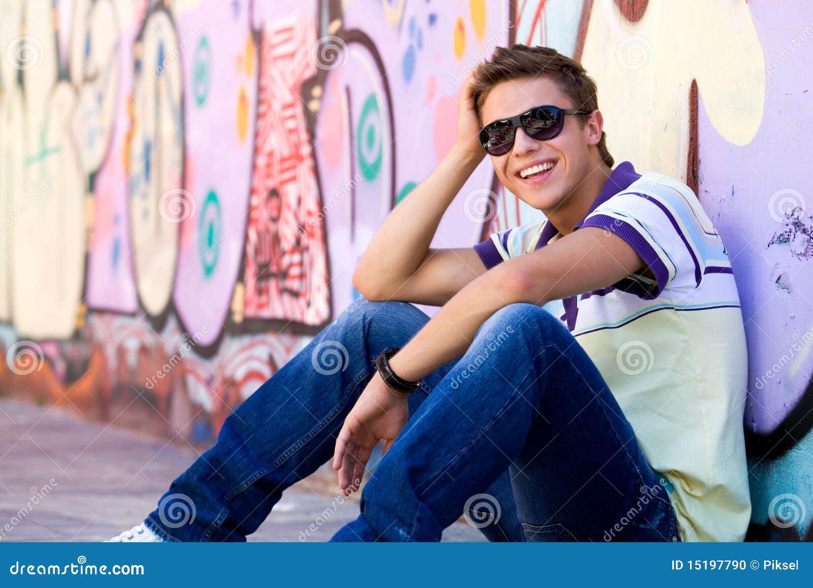 Jonge mens tegen graffitimuur