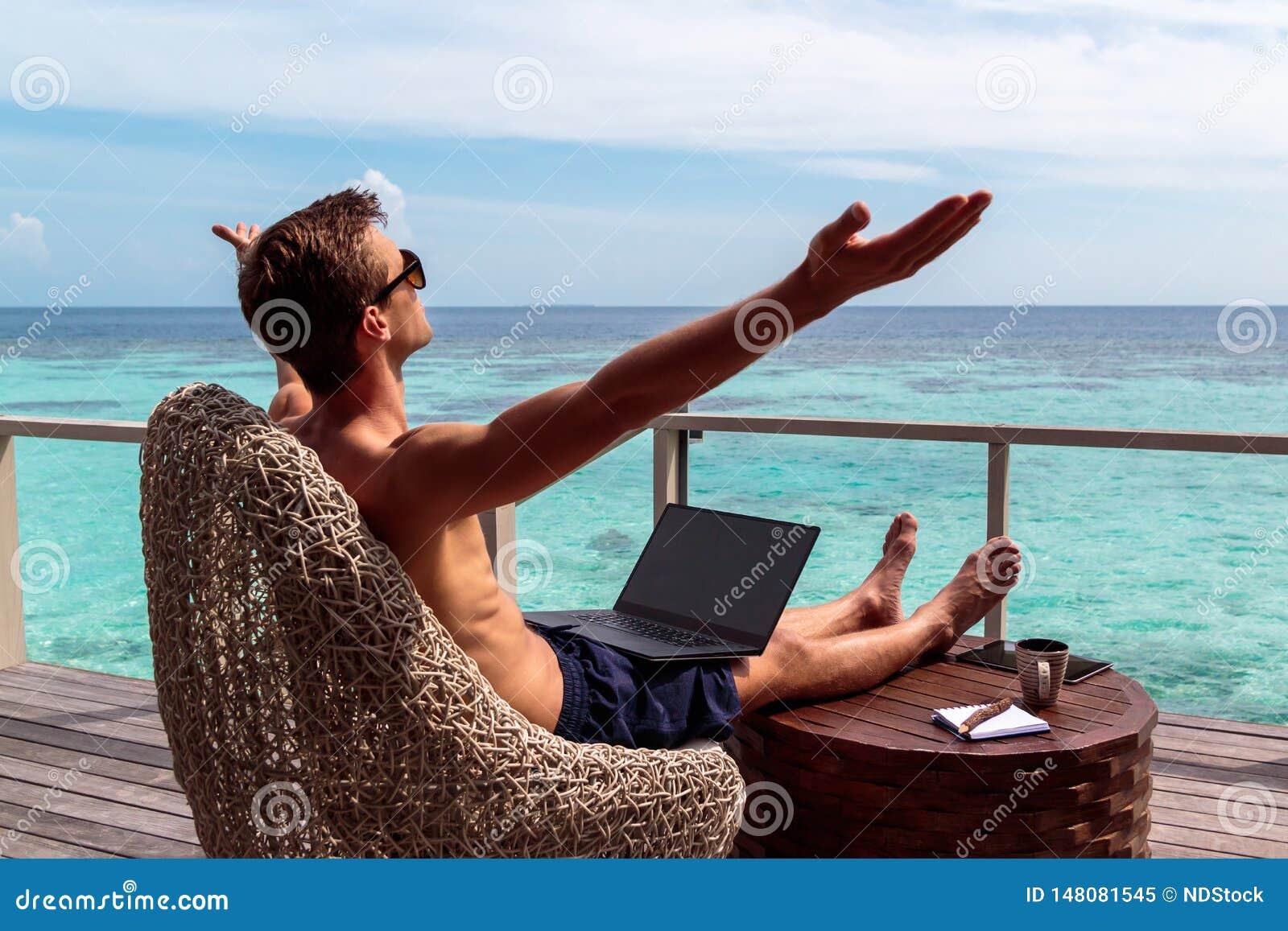 Jonge mens in zwempak die aan laptop in een tropische bestemming werken opgeheven wapens, vrijheidsconcept