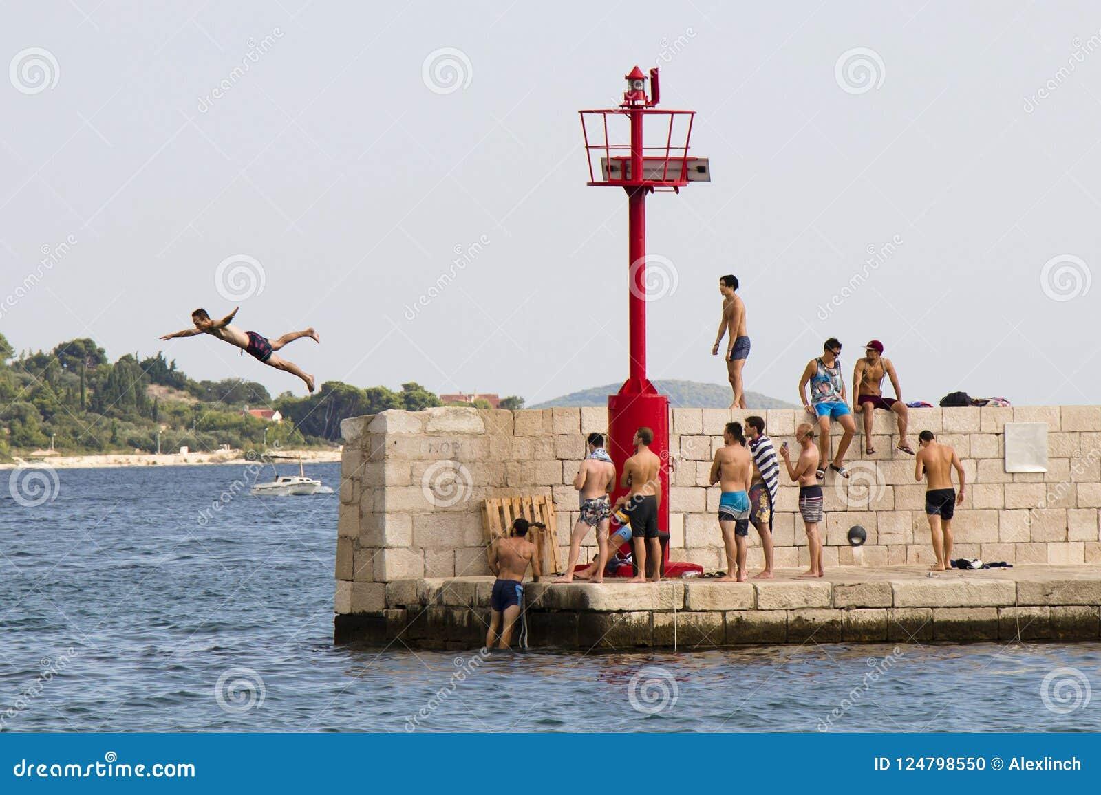 Jonge mensen die in zwempakken op een mens letten springend van de pijler