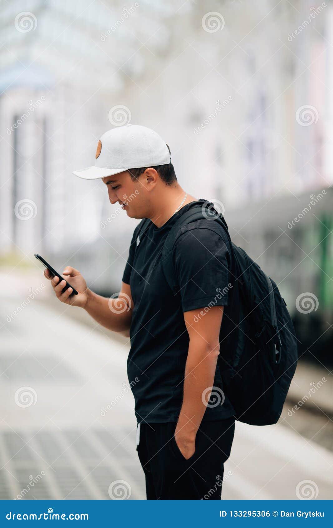 Jonge mensenholding die telefoon met rugzak met behulp van die zich op platform bij station bevinden Reisconcept, exemplaarruimte