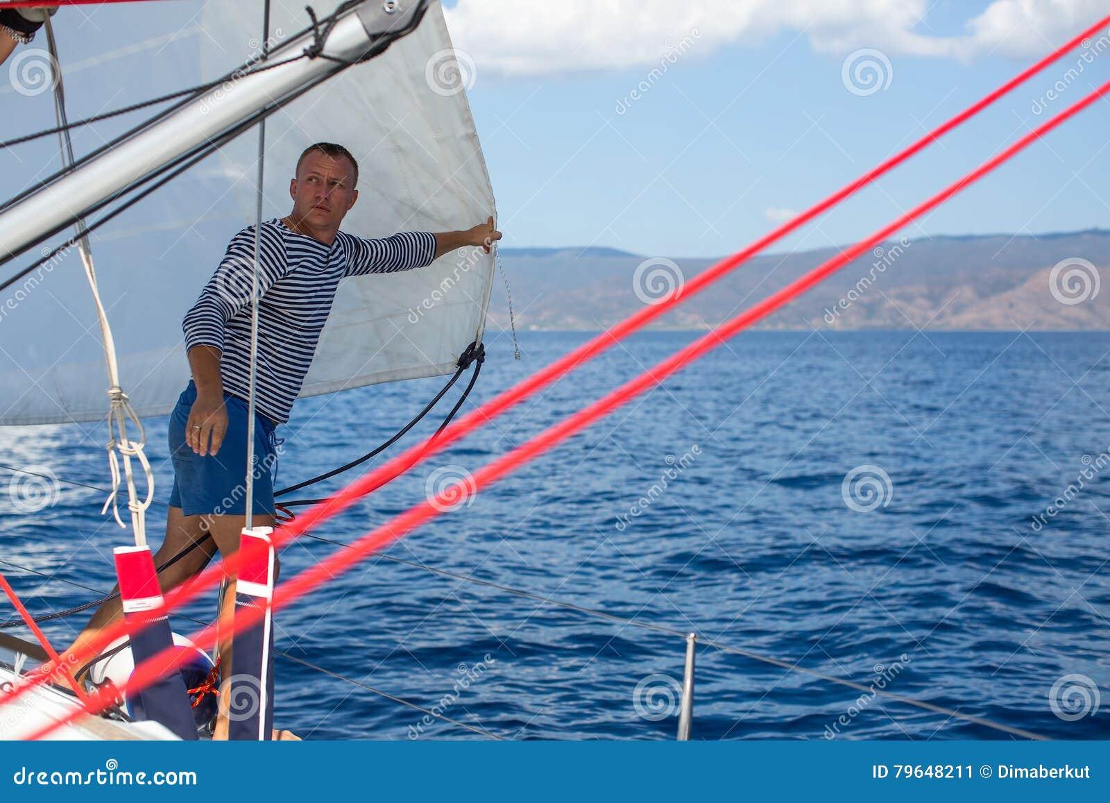 Jonge mensenkapitein - het plaatsen zeilen op de varende jachtboot