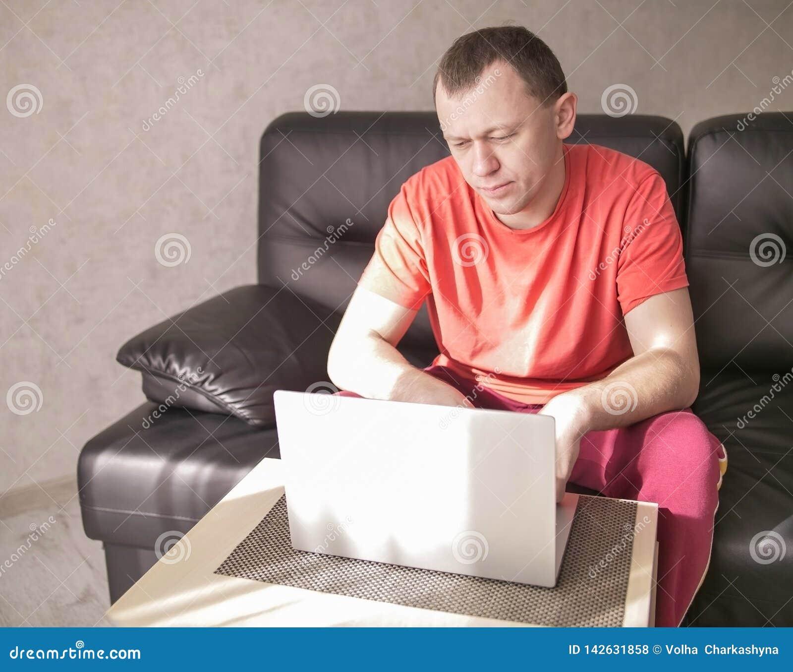Jonge mensenzitting dichtbij laptop in zijn woonkamer op een zonnige middag, copyspace