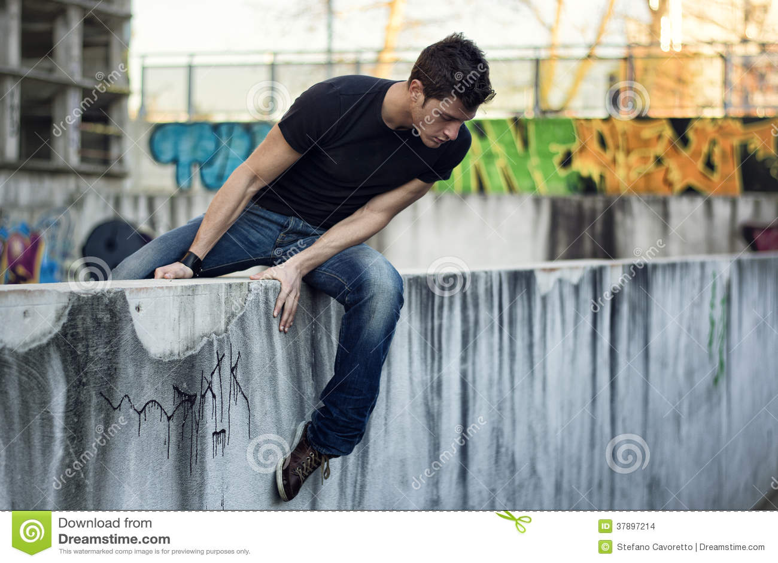 Jonge mensenzitting en het in evenwicht brengen op muur, die neer eruit zien