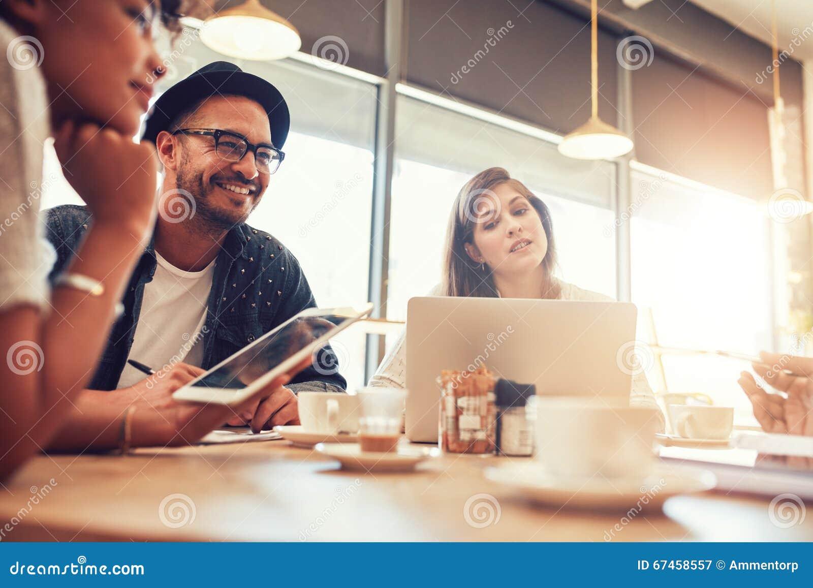 Jonge mensenzitting en het spreken met vrienden bij een koffie