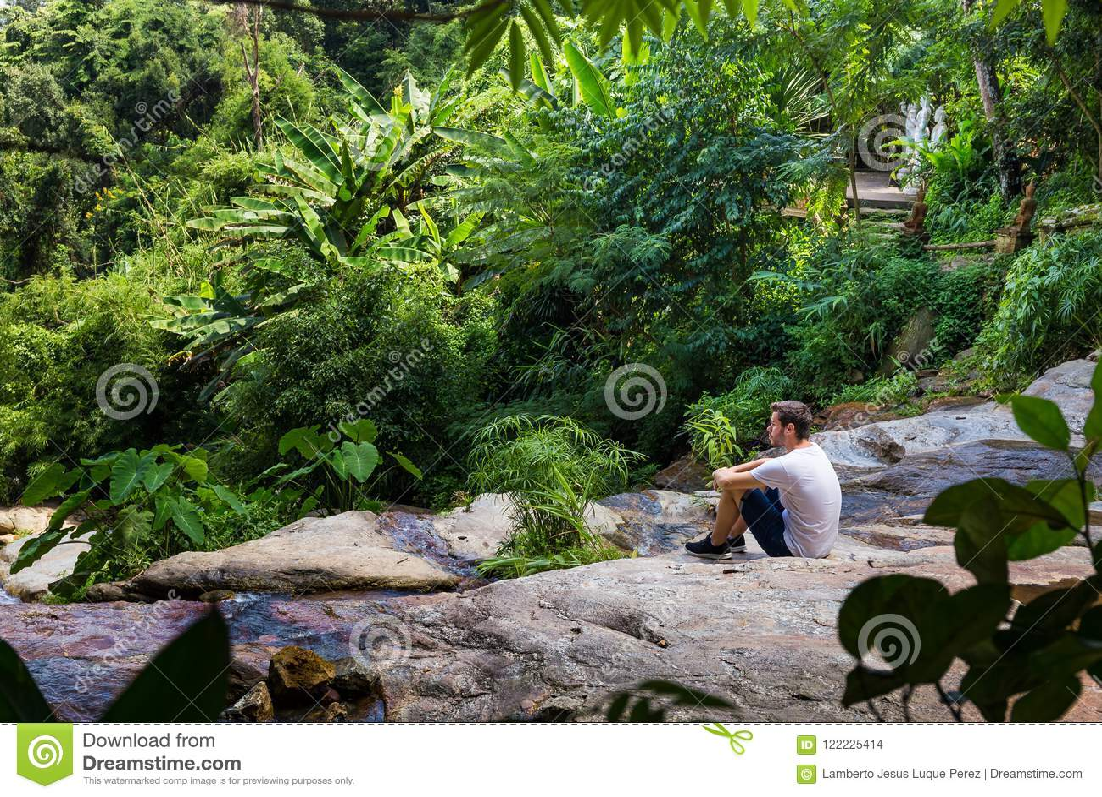 Jonge mensenzitting op een waterval in de wildernis van Chiang Mai