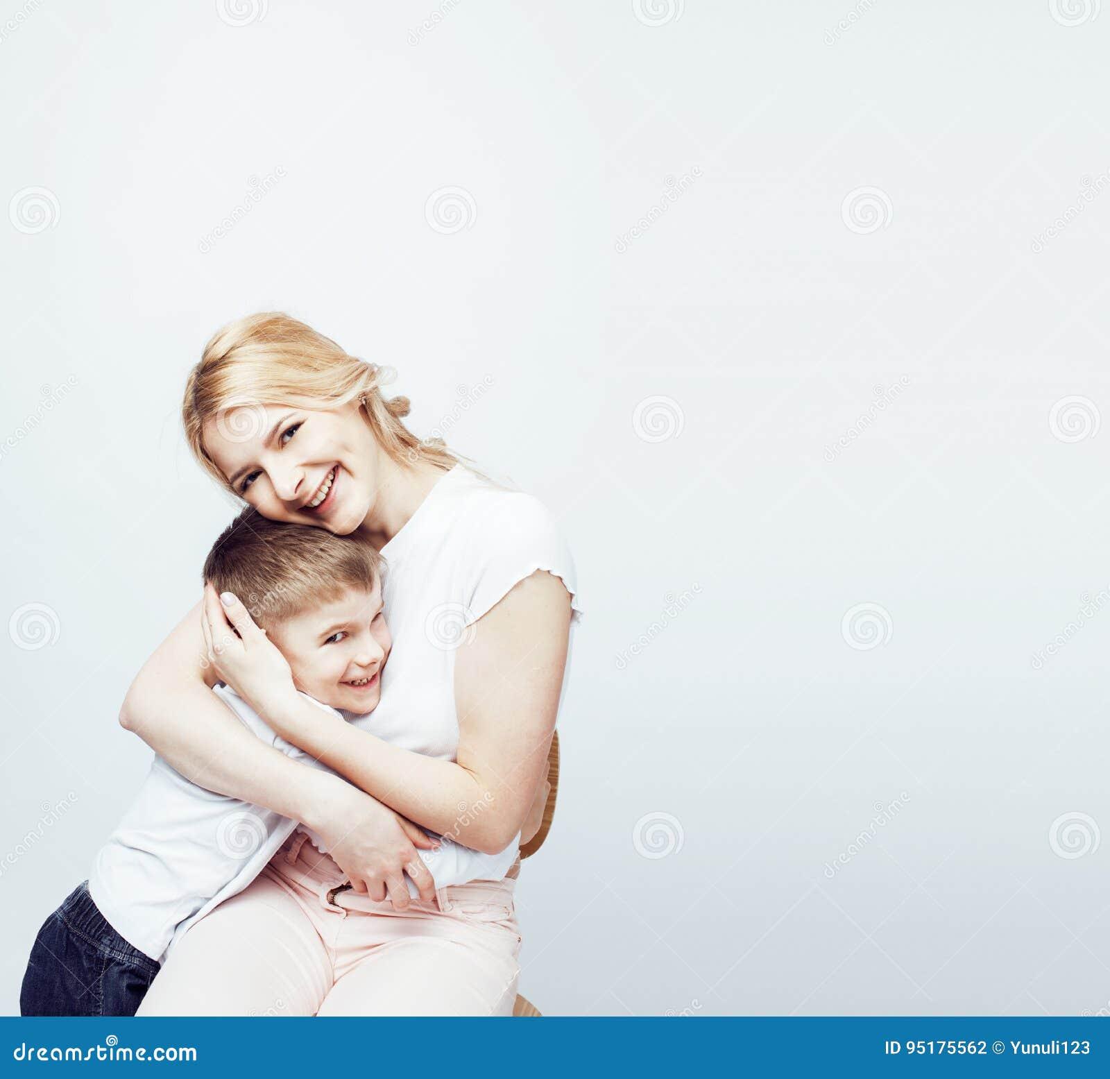 Jonge moderne blonde krullende moeder met het leuke zoon samen gelukkige het glimlachen familie stellen vrolijk op witte achtergr