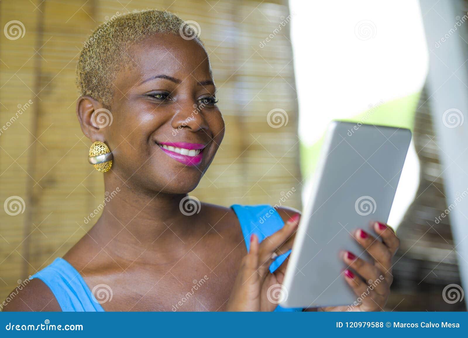 Jonge modieuze en elegante zwarte Afrikaanse Amerikaanse bedrijfsvrouw die bij in koffiewinkel werken die digitaal tabletstootkus