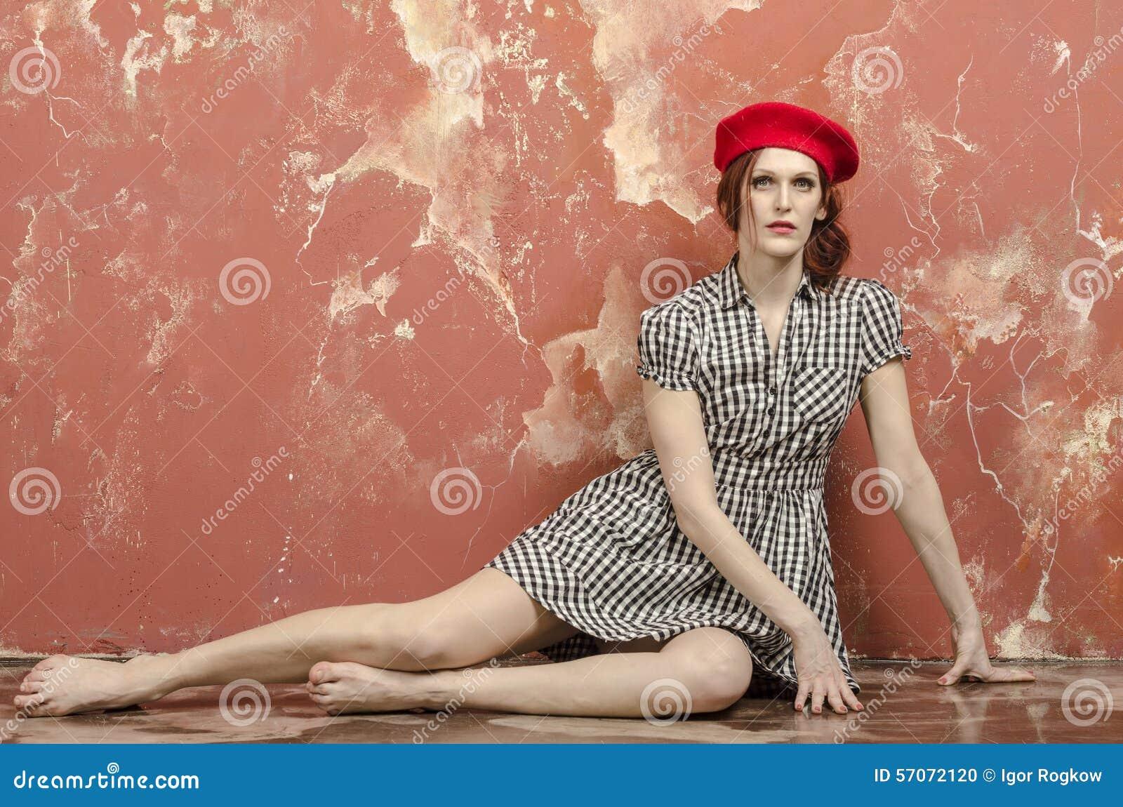 Jonge modieuze vrouw in modieuze kleding in uitstekende stijl en een rode baret
