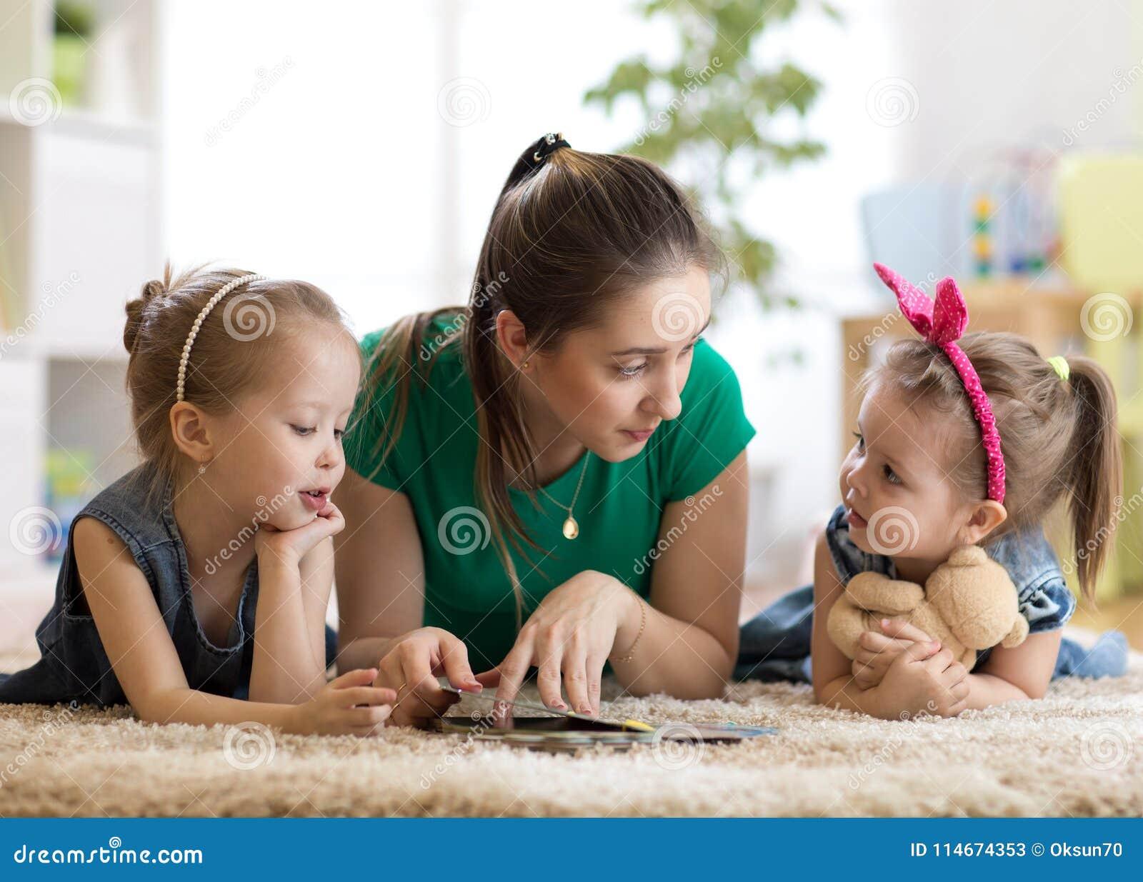 Jonge moeder die een boek lezen aan haar jonge geitjesdochters Kinderen en mamma die op deken in zonnige woonkamer liggen