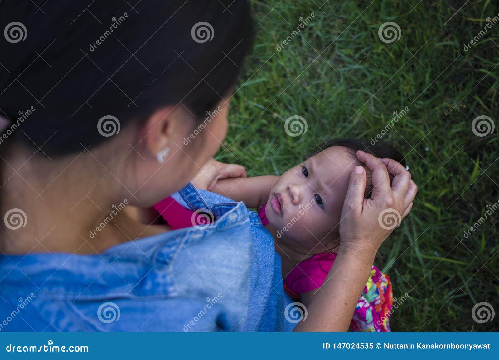 Jonge moeder die en het schreeuwen koesteren kalmeren weinig dochter, Aziatische moeder die haar schreeuwend kind proberen te tro