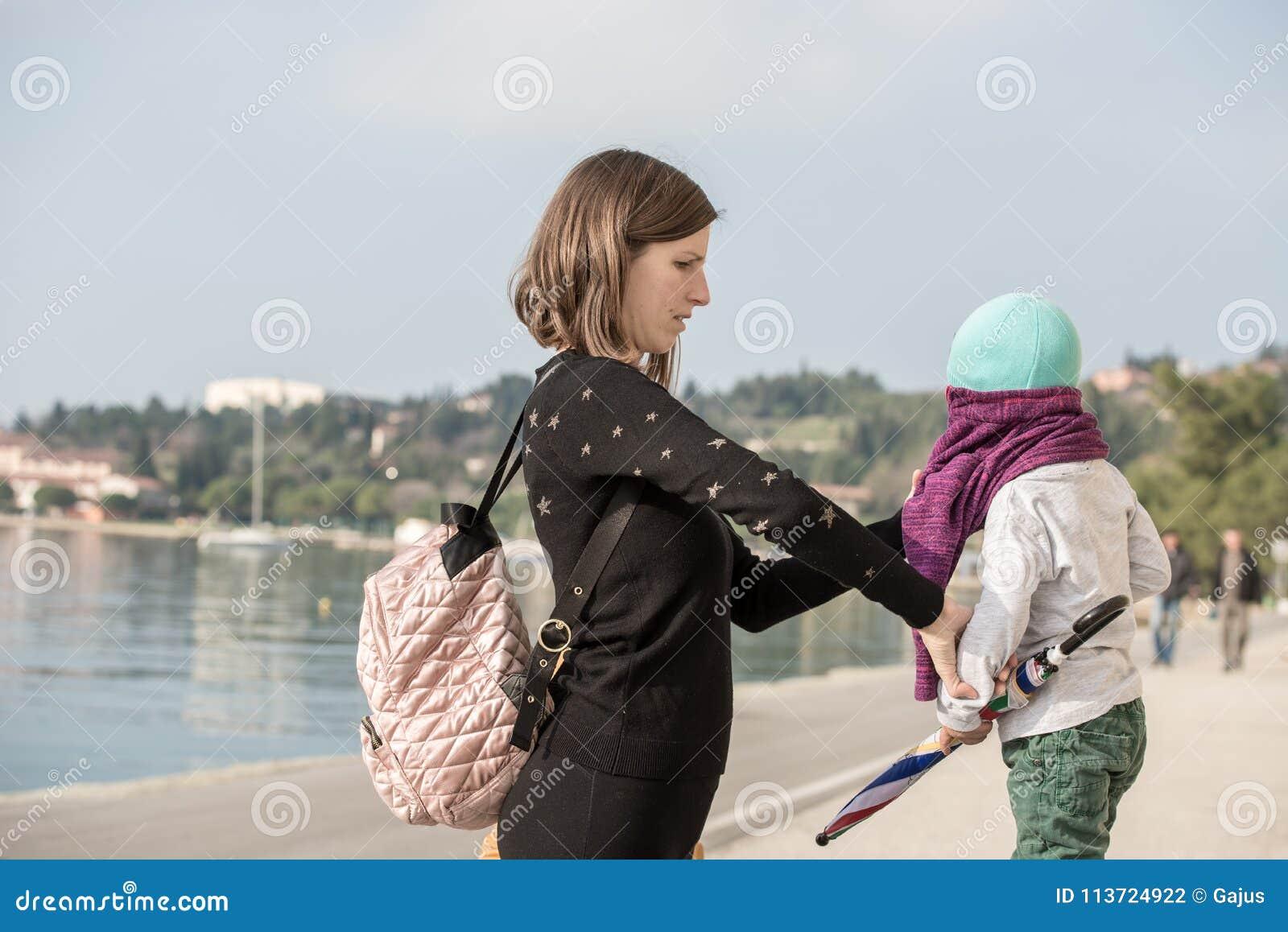 Jonge moeder die haar zoon in een trui kleden