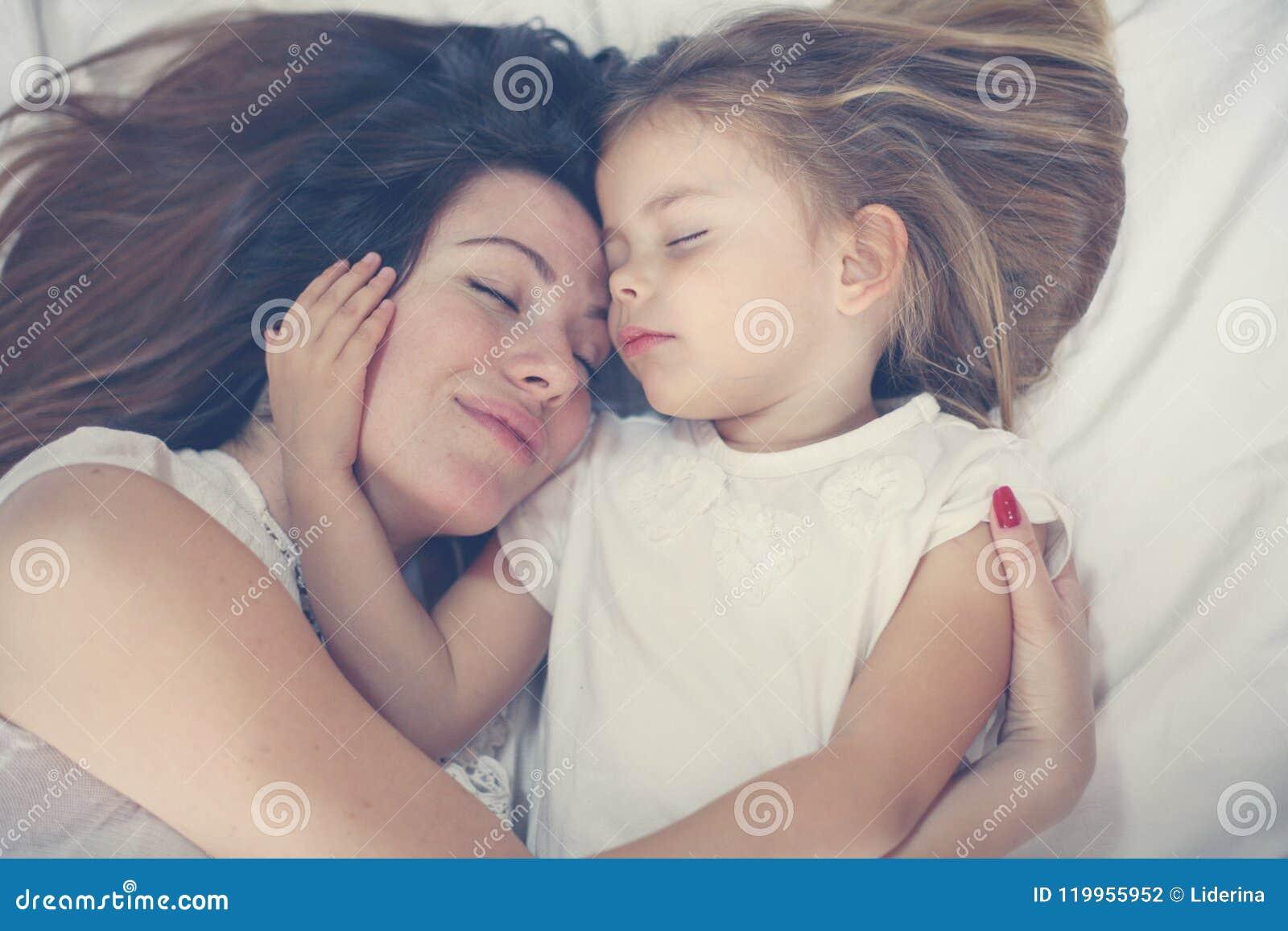 Jonge moeder die met haar weinig dochter op bed spelen Geniet van toge