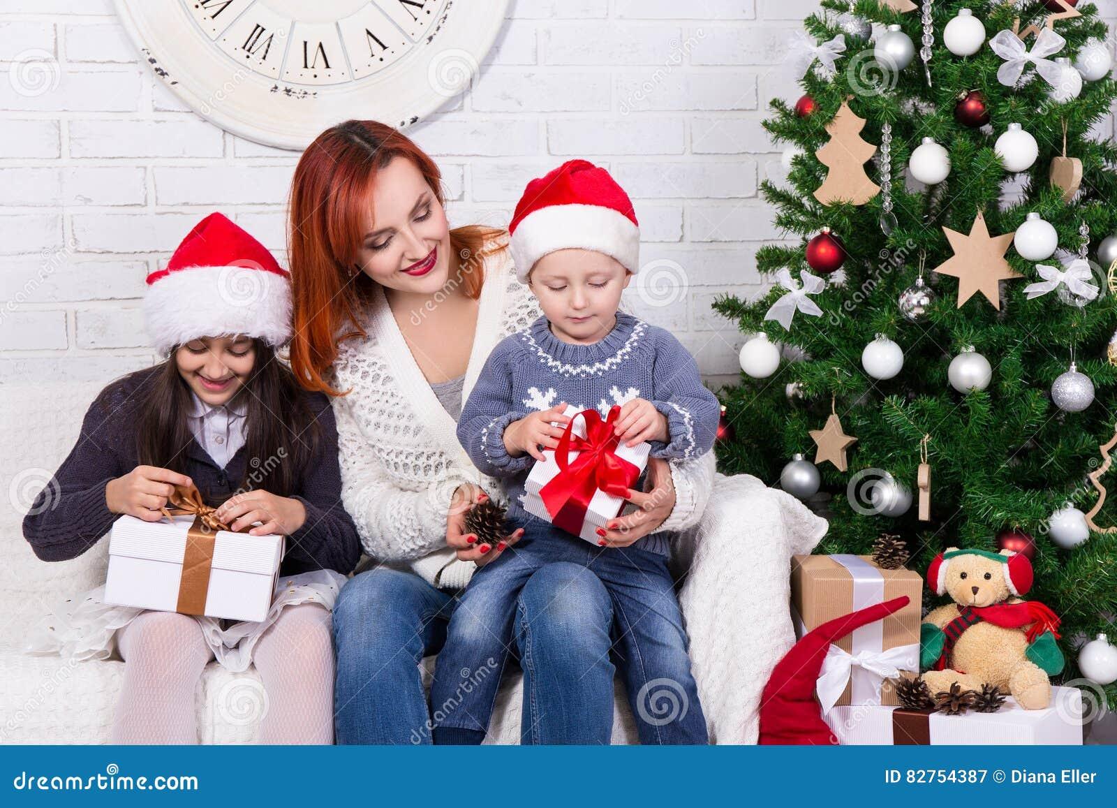 Jonge moeder en kleine jonge geitjes met giftdozen voor Christm