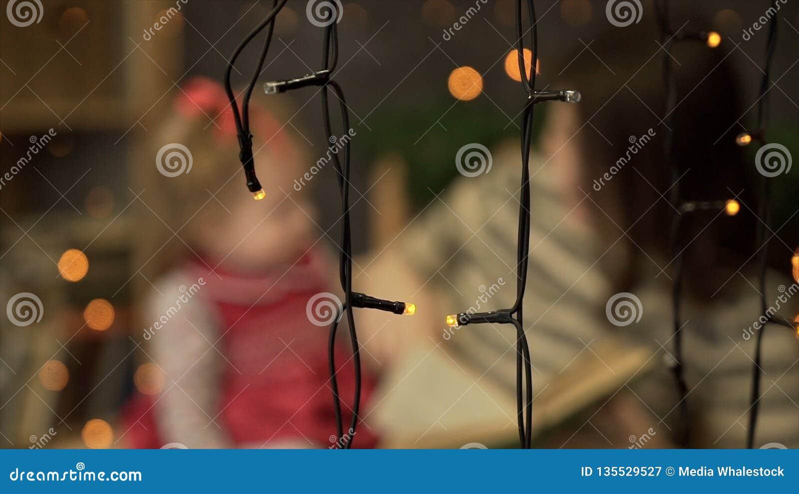 Jonge moeder met weinig boek van de dochterlezing thuis Mamma en weinig dochter die op achtergrond van slingers spelen blur