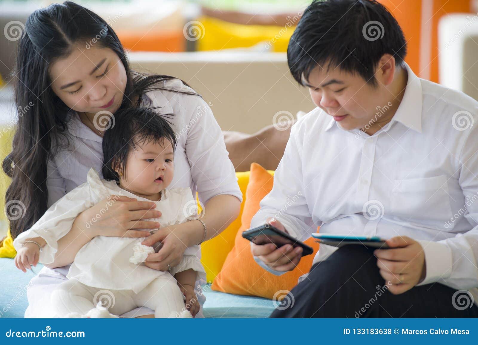Jonge mooie Aziatische Chinese familiezitting bij moderne toevlucht met de werkende zaken van de werkverslaafdemens online met di