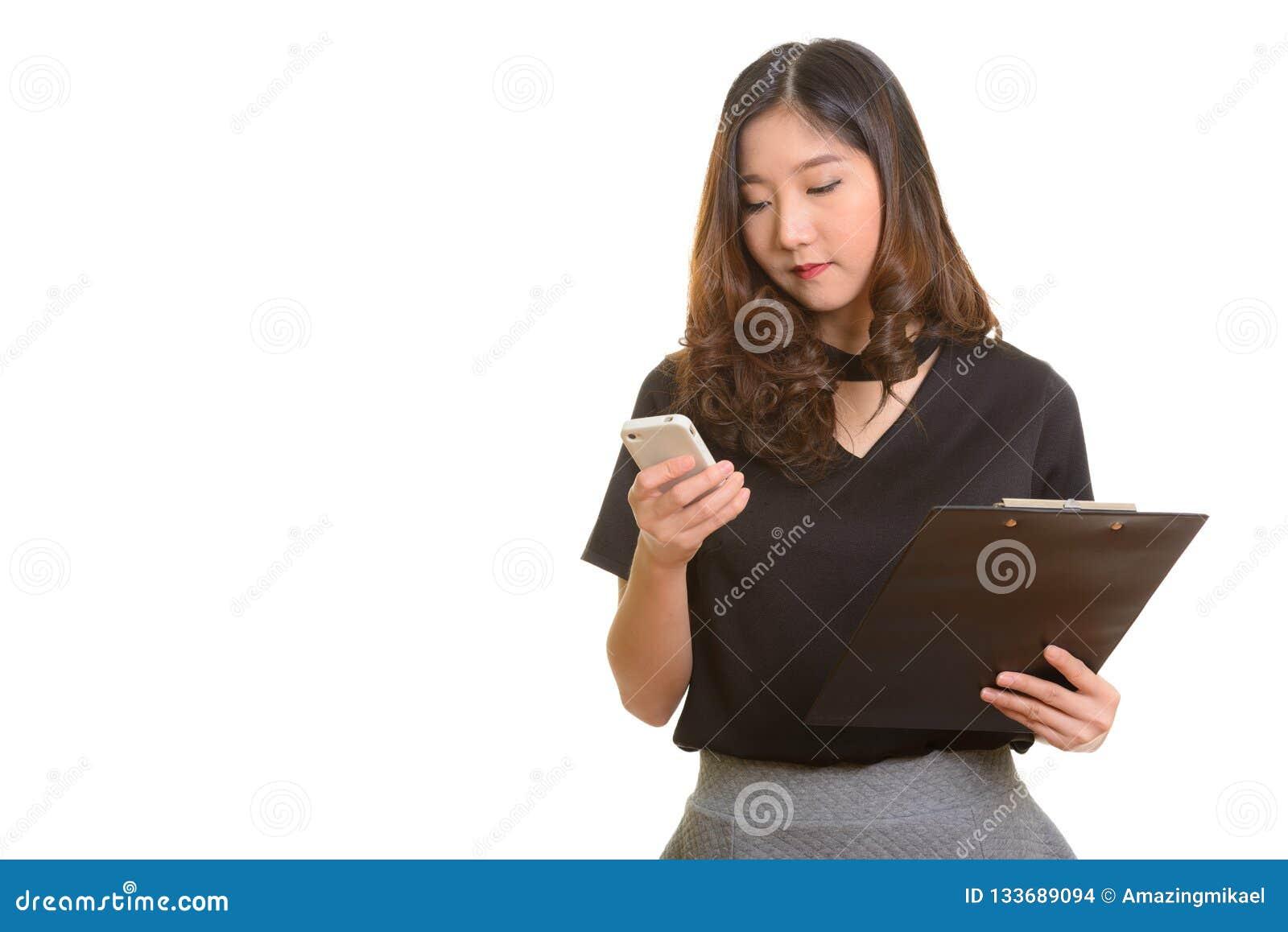 Jonge mooie Aziatische onderneemster die mobiele telefoon met behulp van terwijl HOL