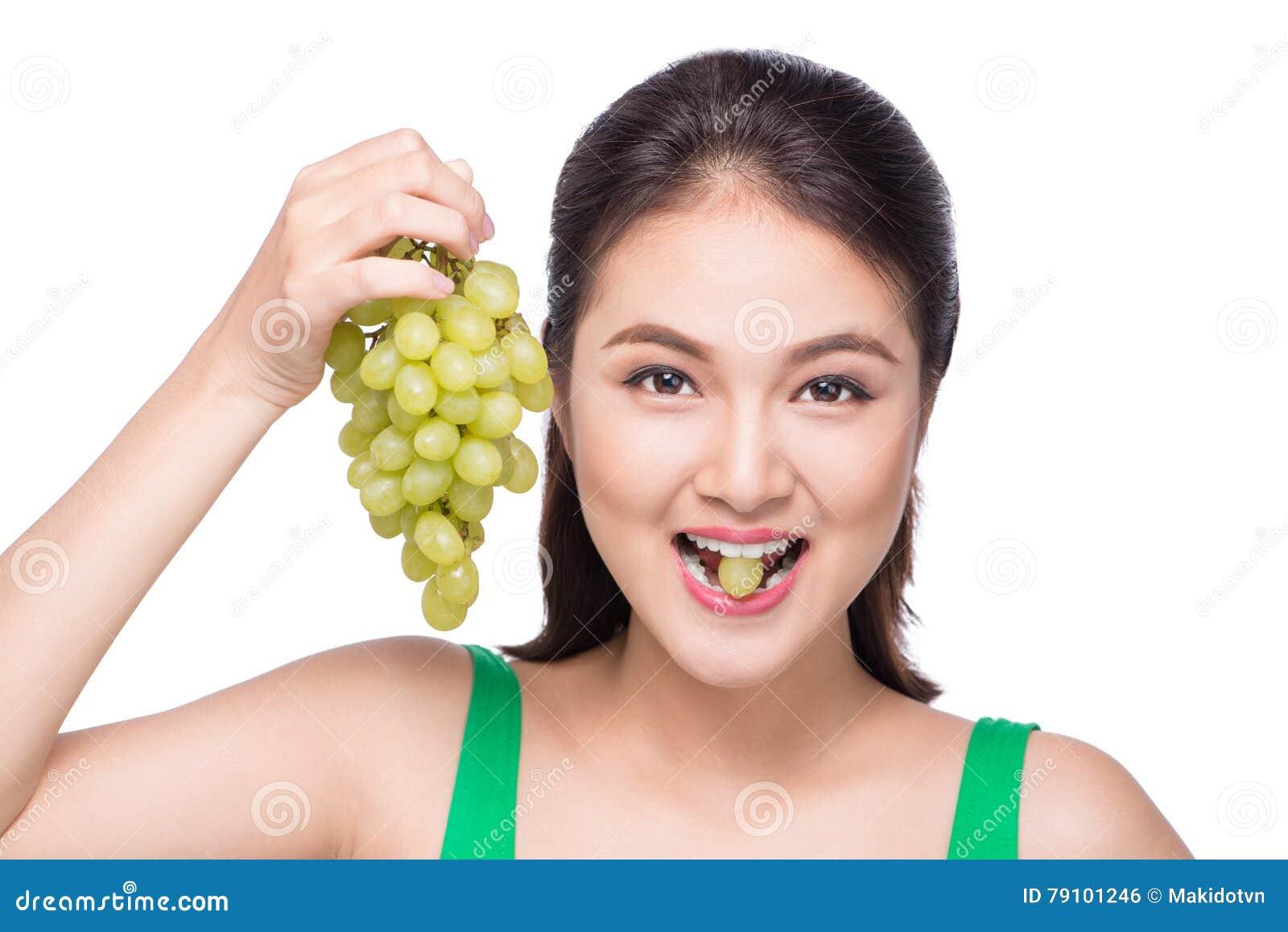 Jonge mooie Aziatische vrouw die verse die druiven eten op whit worden geïsoleerd